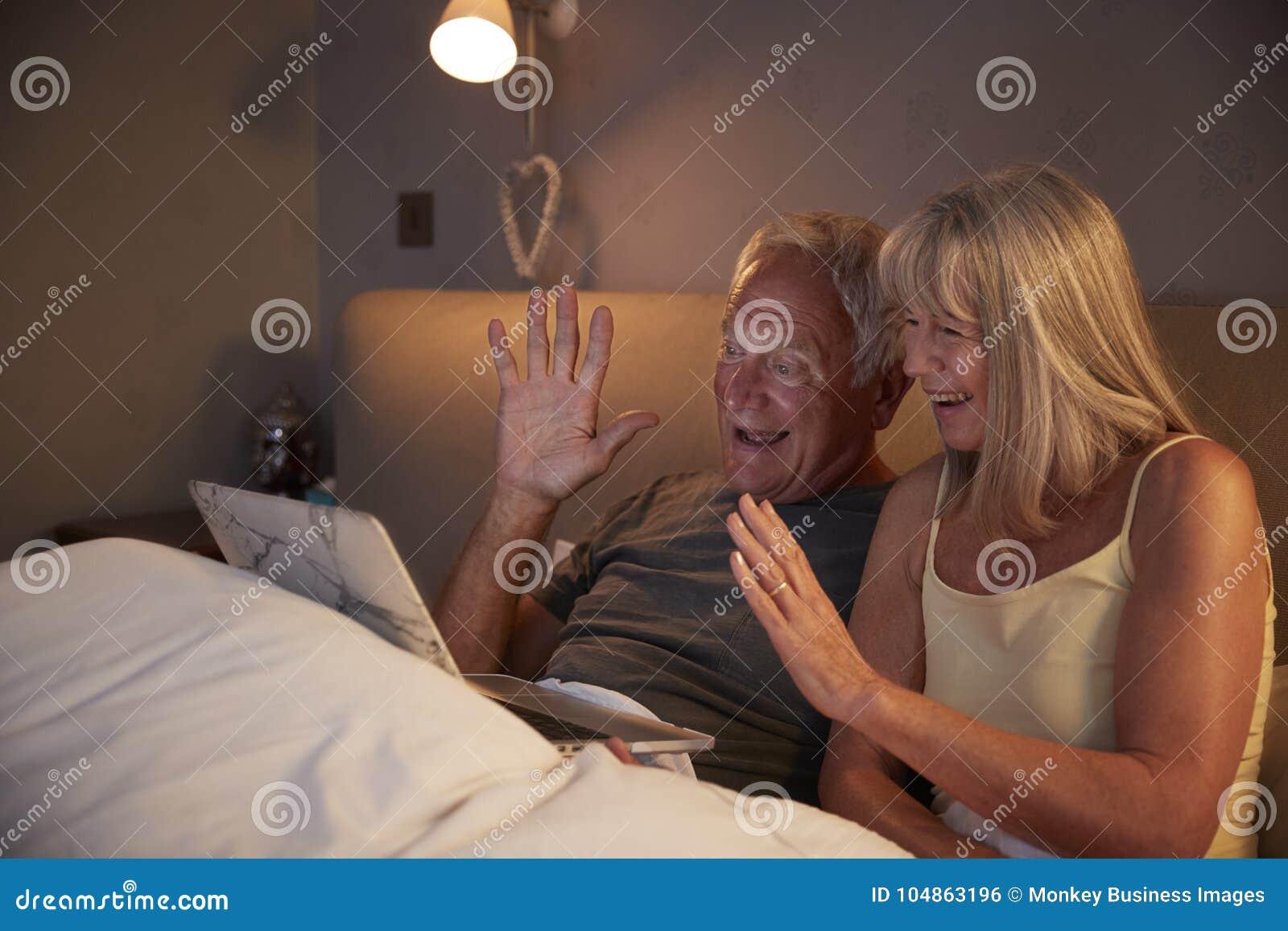 Coppie senior facendo uso del computer portatile da collegarsi con la famiglia per la video chiamata