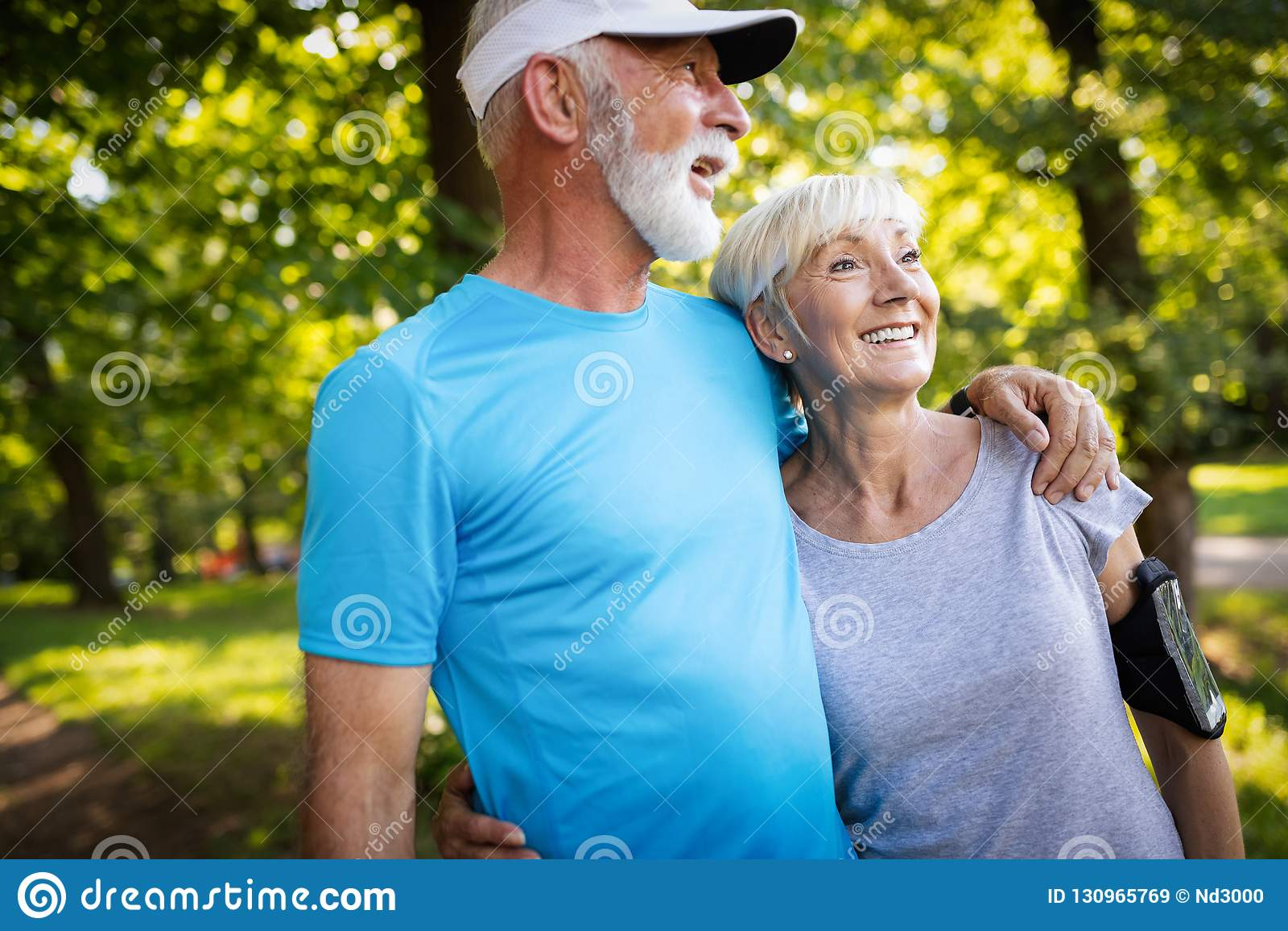 Coppie senior felici che restano misura tramite il funzionamento di sport
