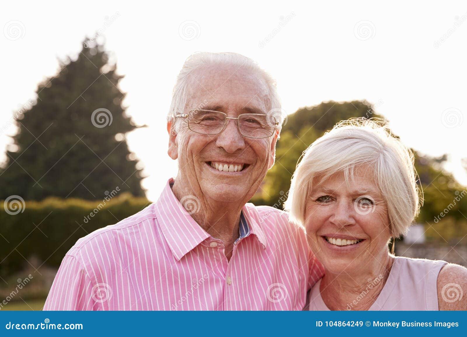 Coppie senior in giardino che sorride alla macchina fotografica, fine su