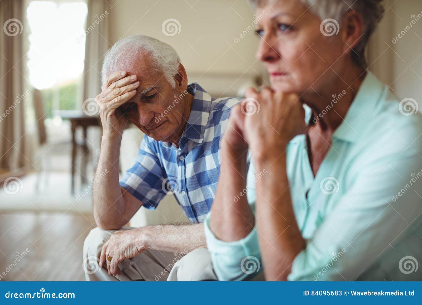 Coppie senior turbate che si rilassano sul sofà