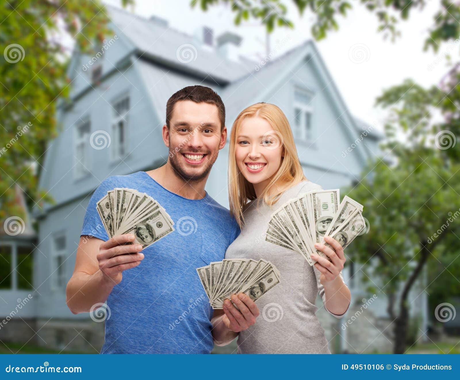 Coppie sorridenti che mostrano soldi sopra il fondo della casa