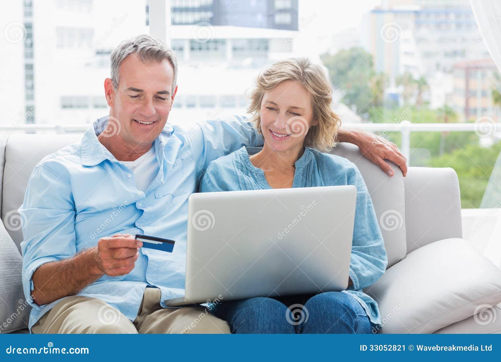 Coppie sorridenti che si siedono sul loro strato facendo uso del computer portatile per comprare sopra