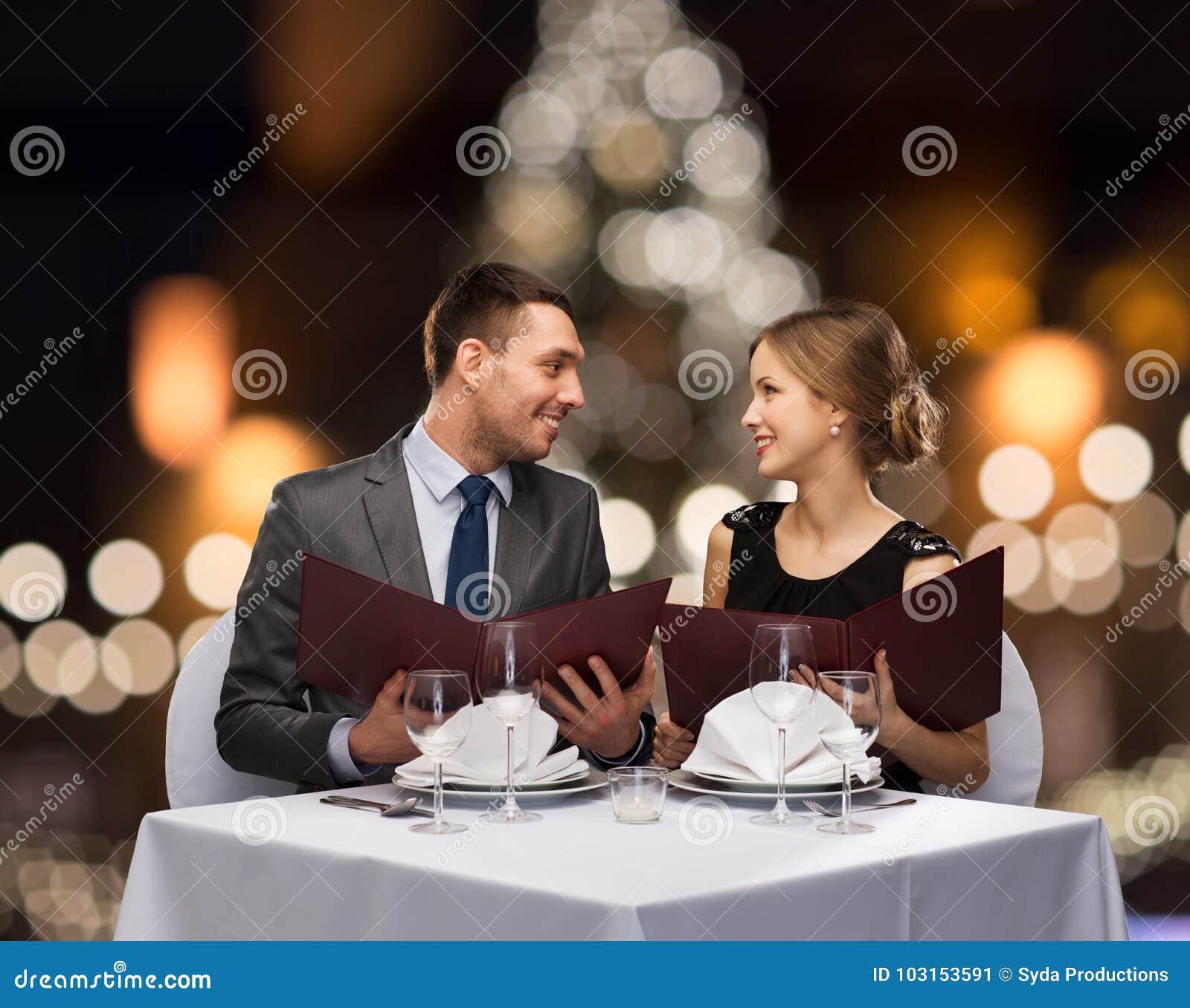 Coppie sorridenti con i menu al ristorante di natale