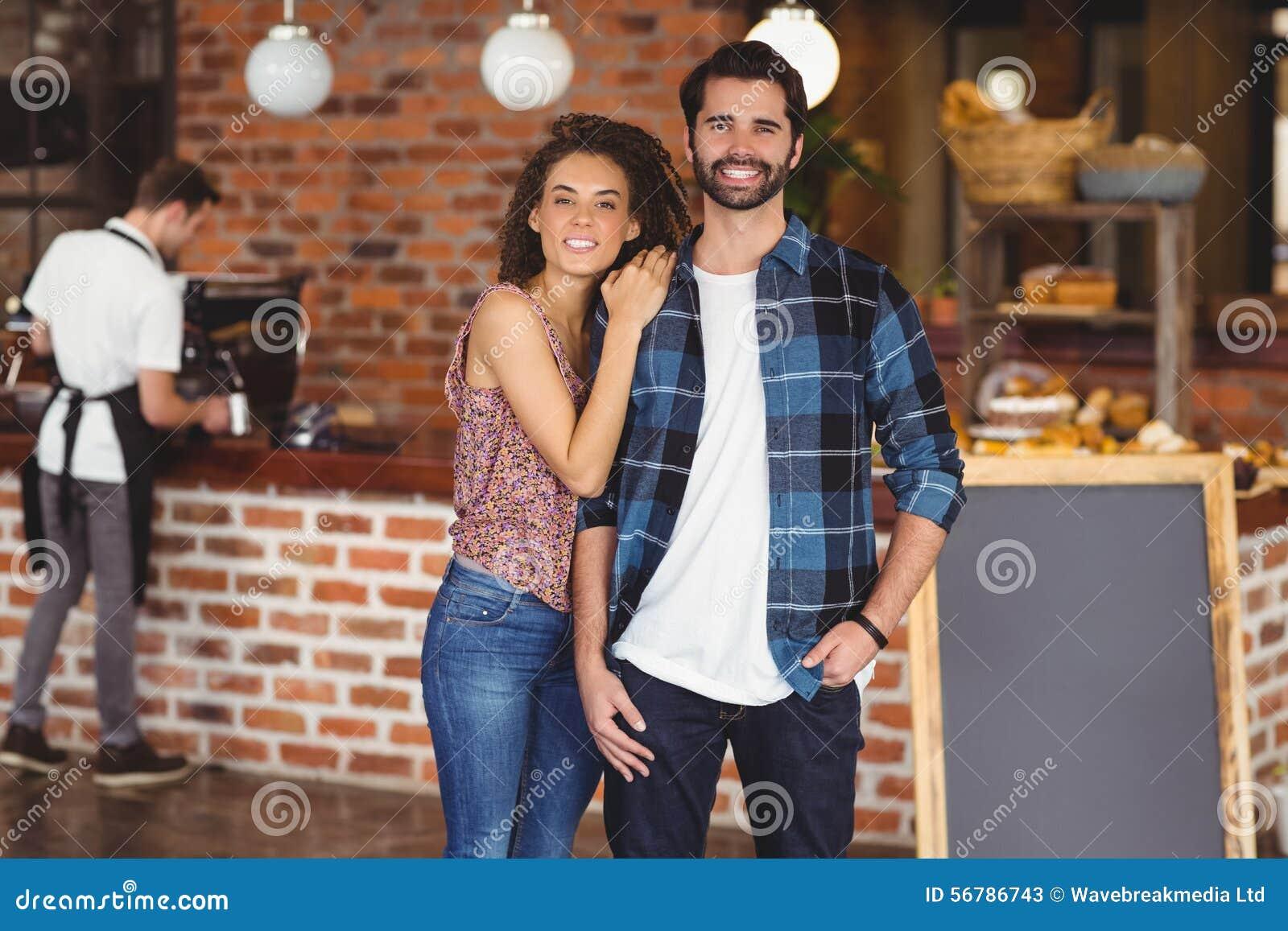 Coppie sorridenti dei pantaloni a vita bassa davanti al barista