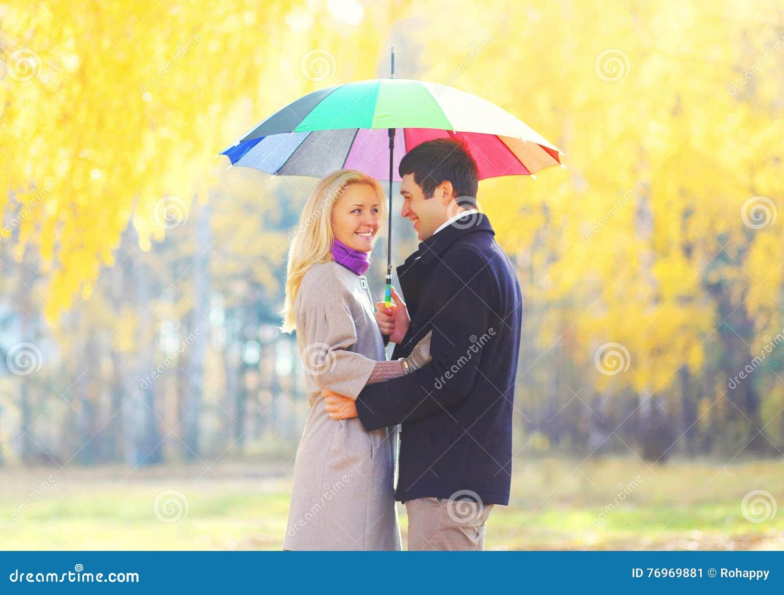 Coppie sorridenti di amore felici con l ombrello variopinto in soleggiato caldo