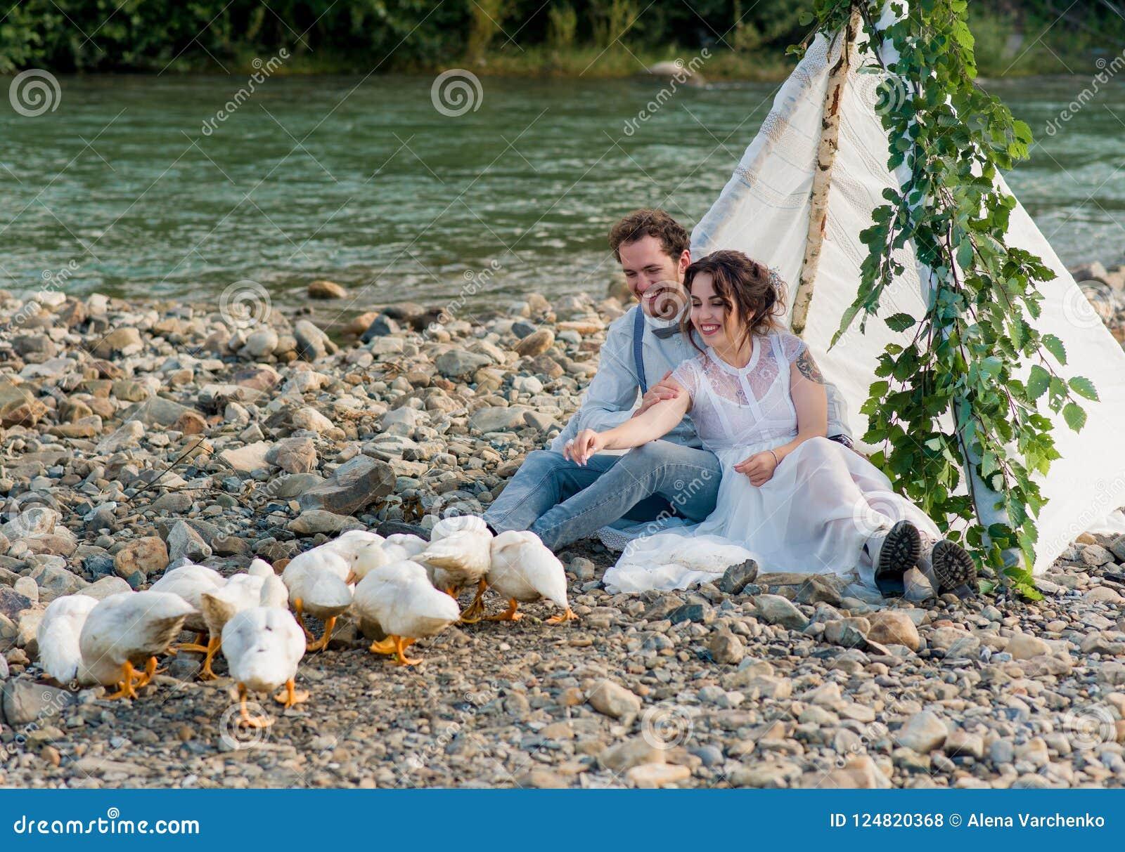 Coppie, sposo e sposa di nozze sui precedenti di una torrente montano
