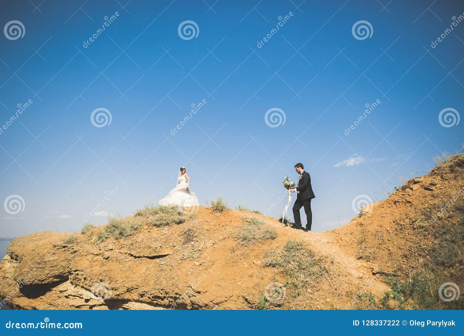 Coppie, sposo, sposa con il mazzo che posa vicino al mare e cielo blu di nozze