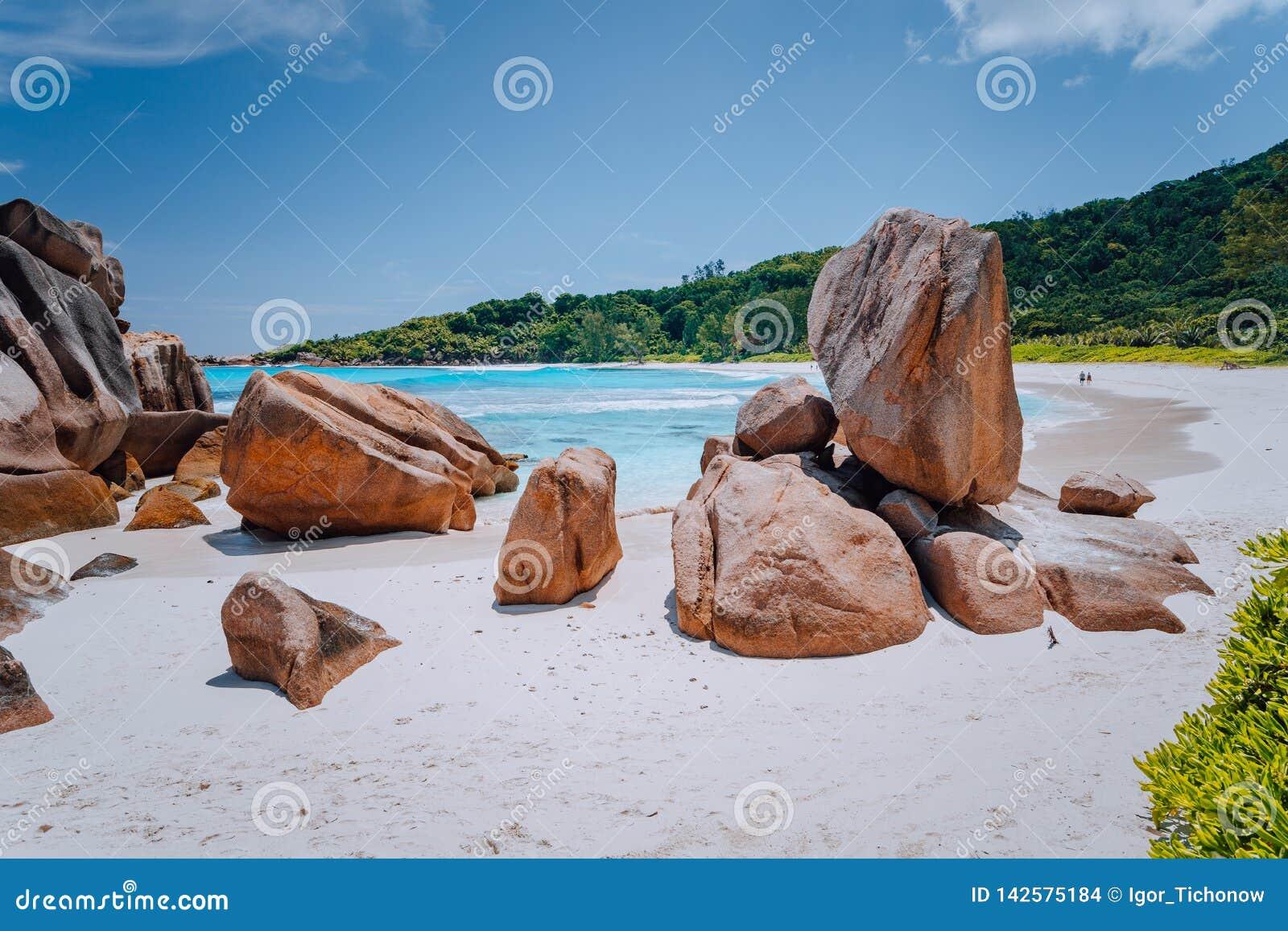 Coppie sulla laguna tropicale della spiaggia con i massi del granito nell acqua del turchese ed in una sabbia bianca incontaminat