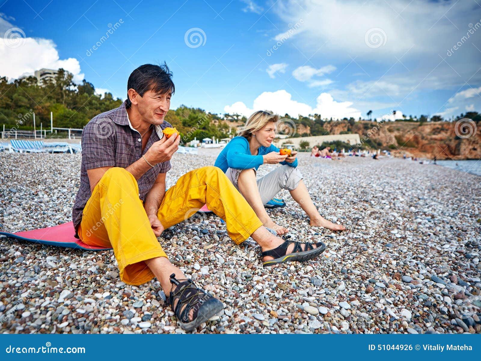 Coppie sulla spiaggia che mangia i cachi