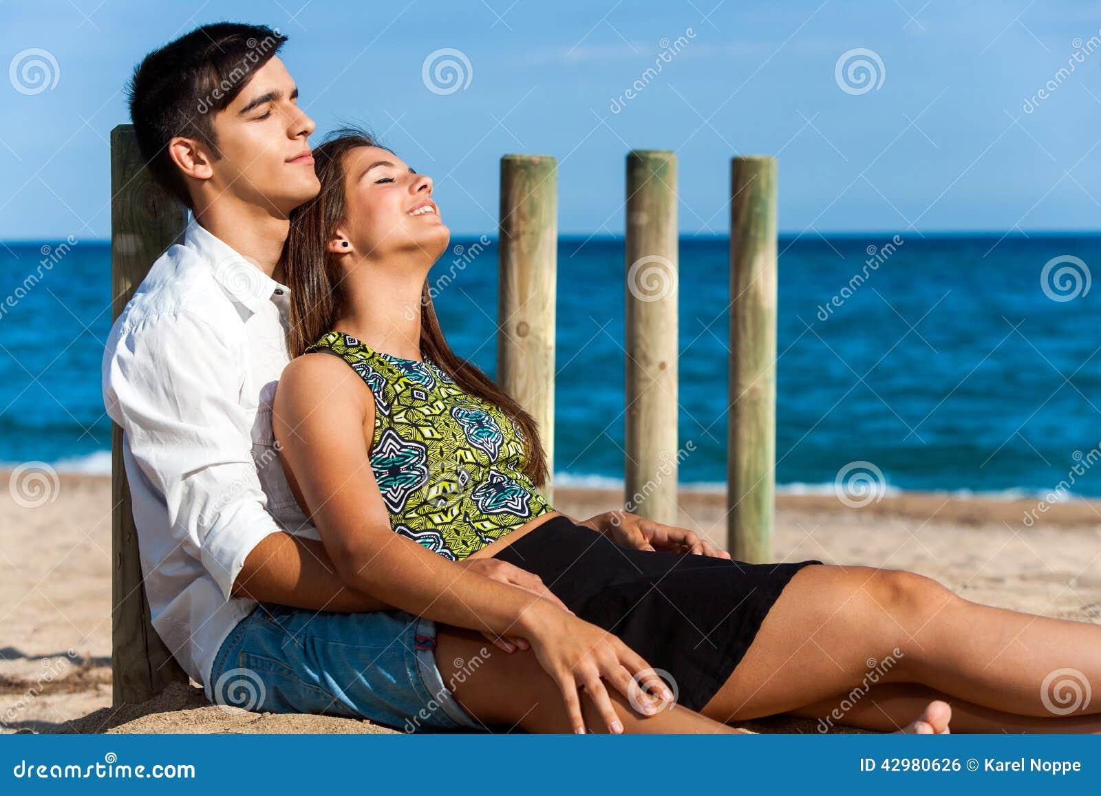 Coppie sveglie che si rilassano sulla spiaggia