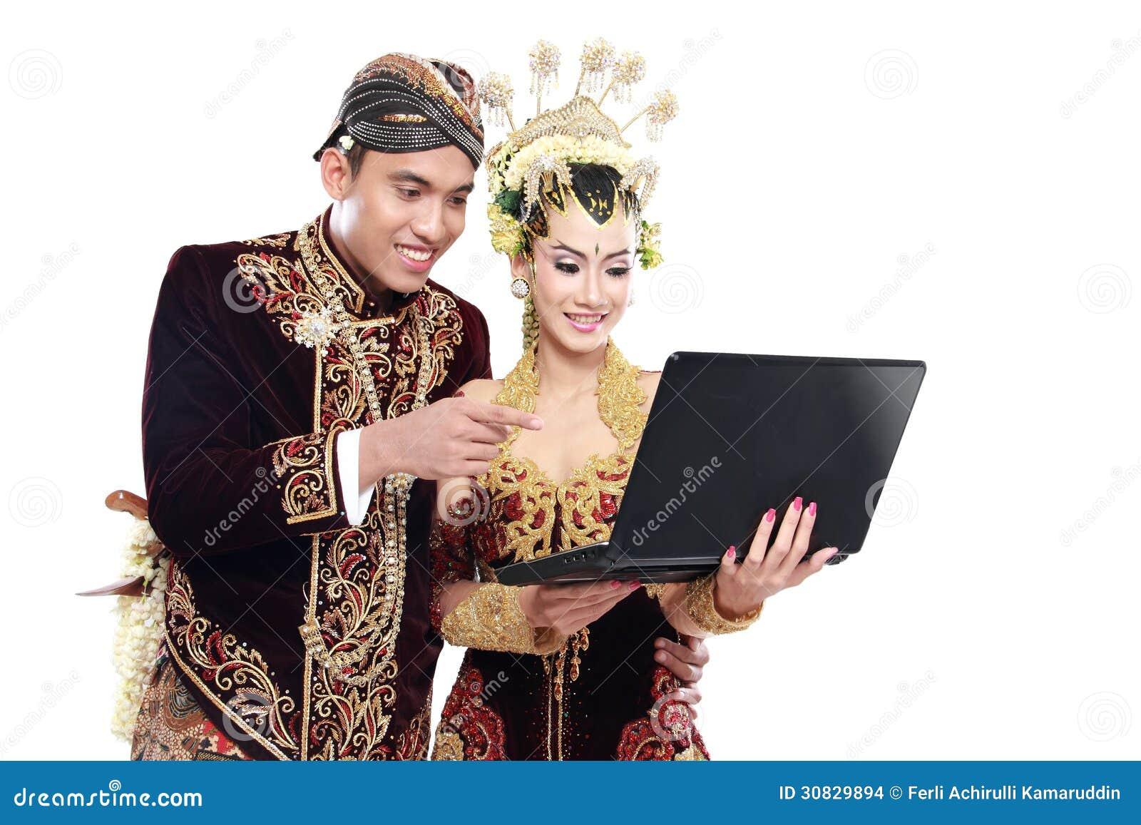 Coppie tradizionali felici di nozze di Java con il computer portatile