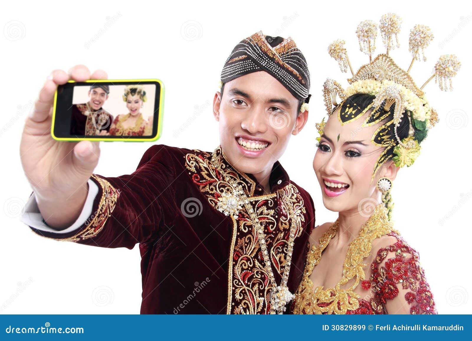Coppie tradizionali felici di nozze di Java con il telefono cellulare