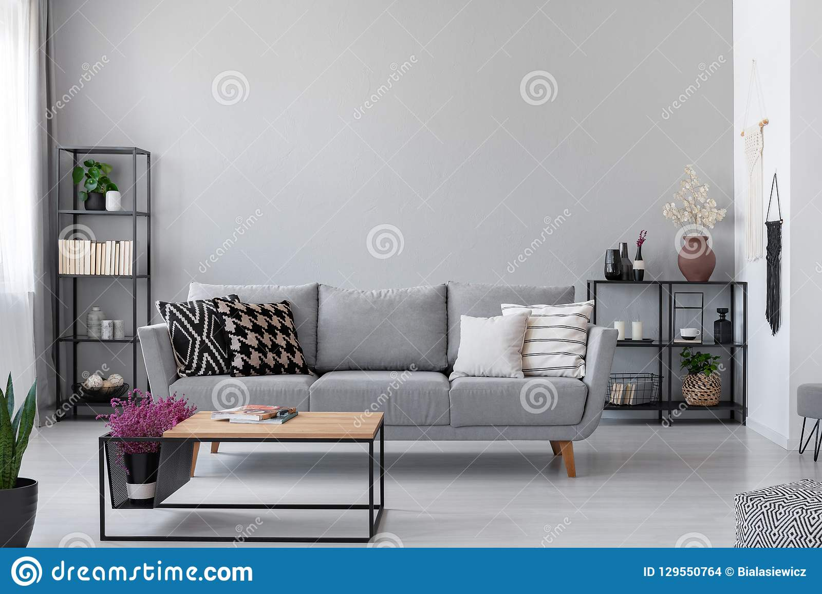Copy space on the wall of scandinavian living room with modern couch, metal shelves and industrial coffee table