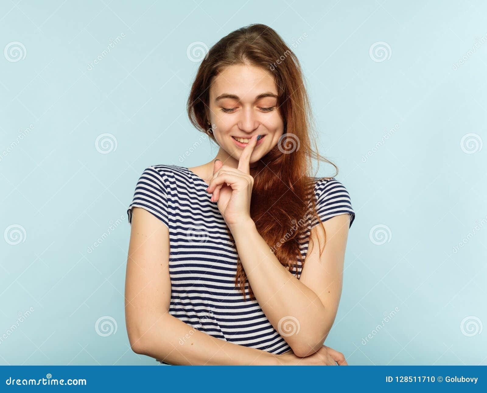 Coquettish attractive girl secret finger on lips