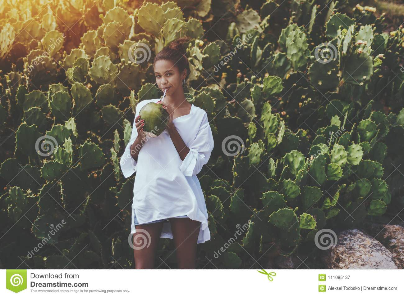 Afro girl drinking coco water from coconut near cactuses