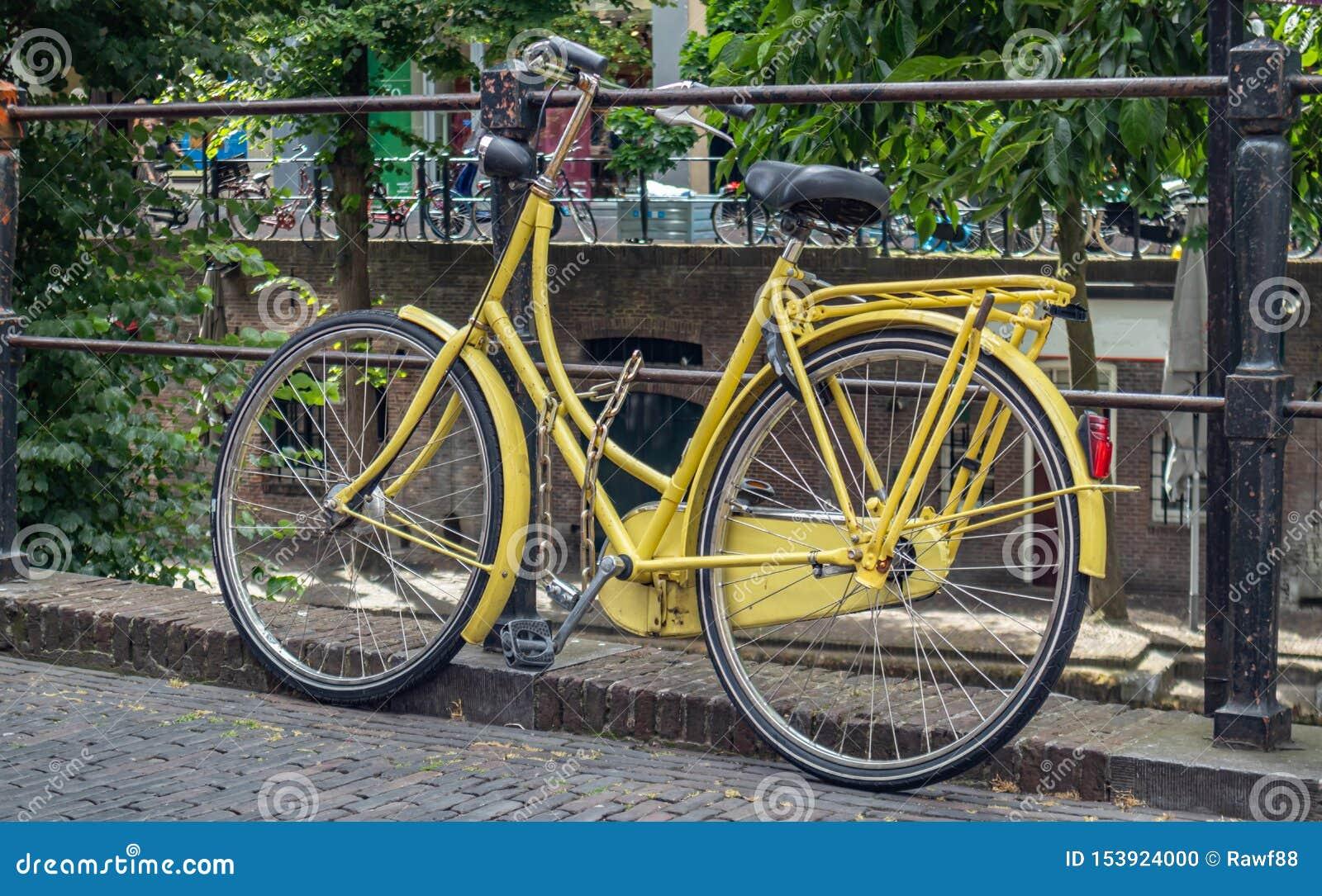 Cor amarela da bicicleta travada em um trilho do canal do rio na cidade de Utrecht, Países Baixos