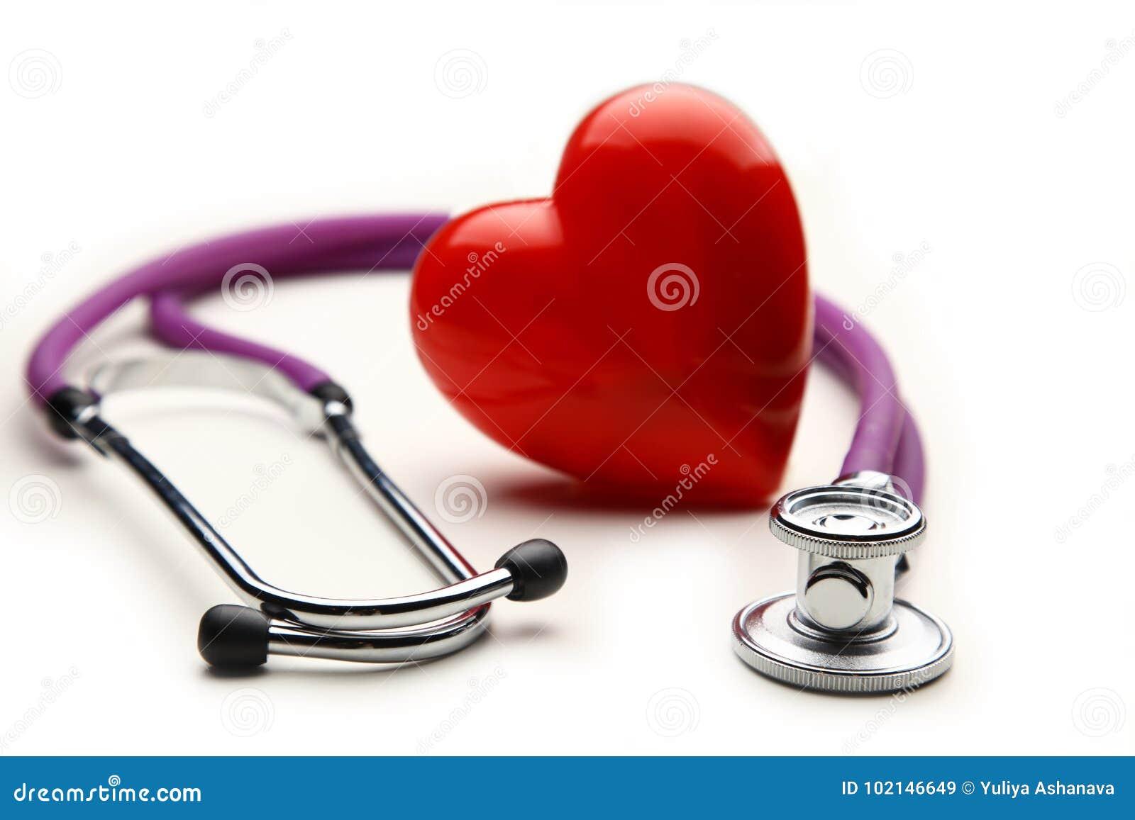 Coração com um estetoscópio médico, isolado no fundo de madeira