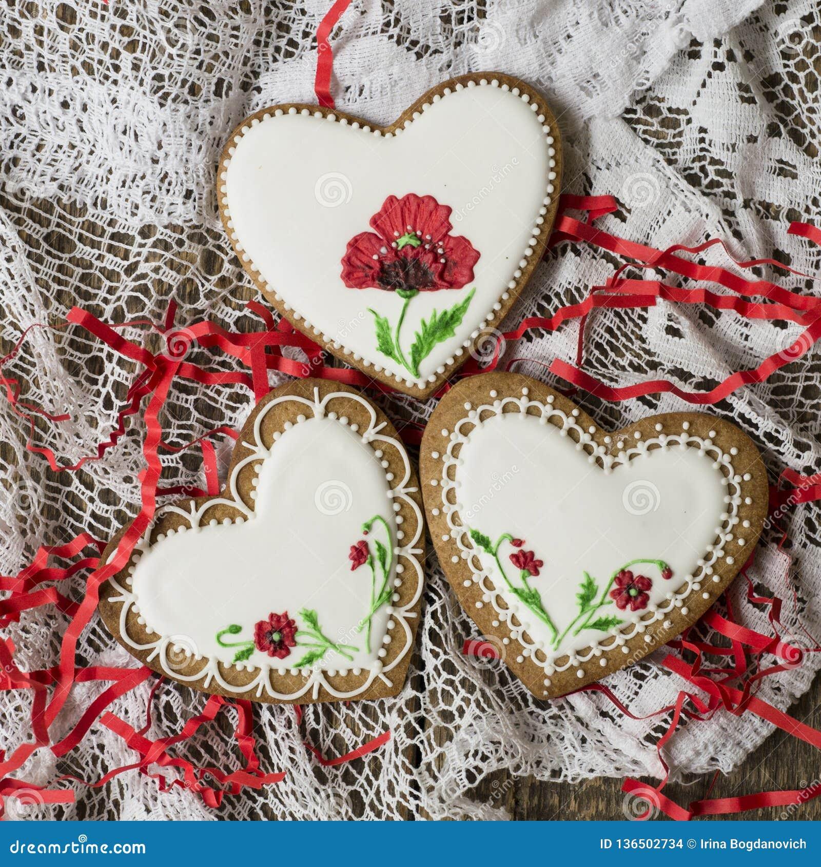 Coração das cookies decorado com as papoilas vermelhas no estilo do vintage no fundo de madeira para o dia de Valentim Presente p
