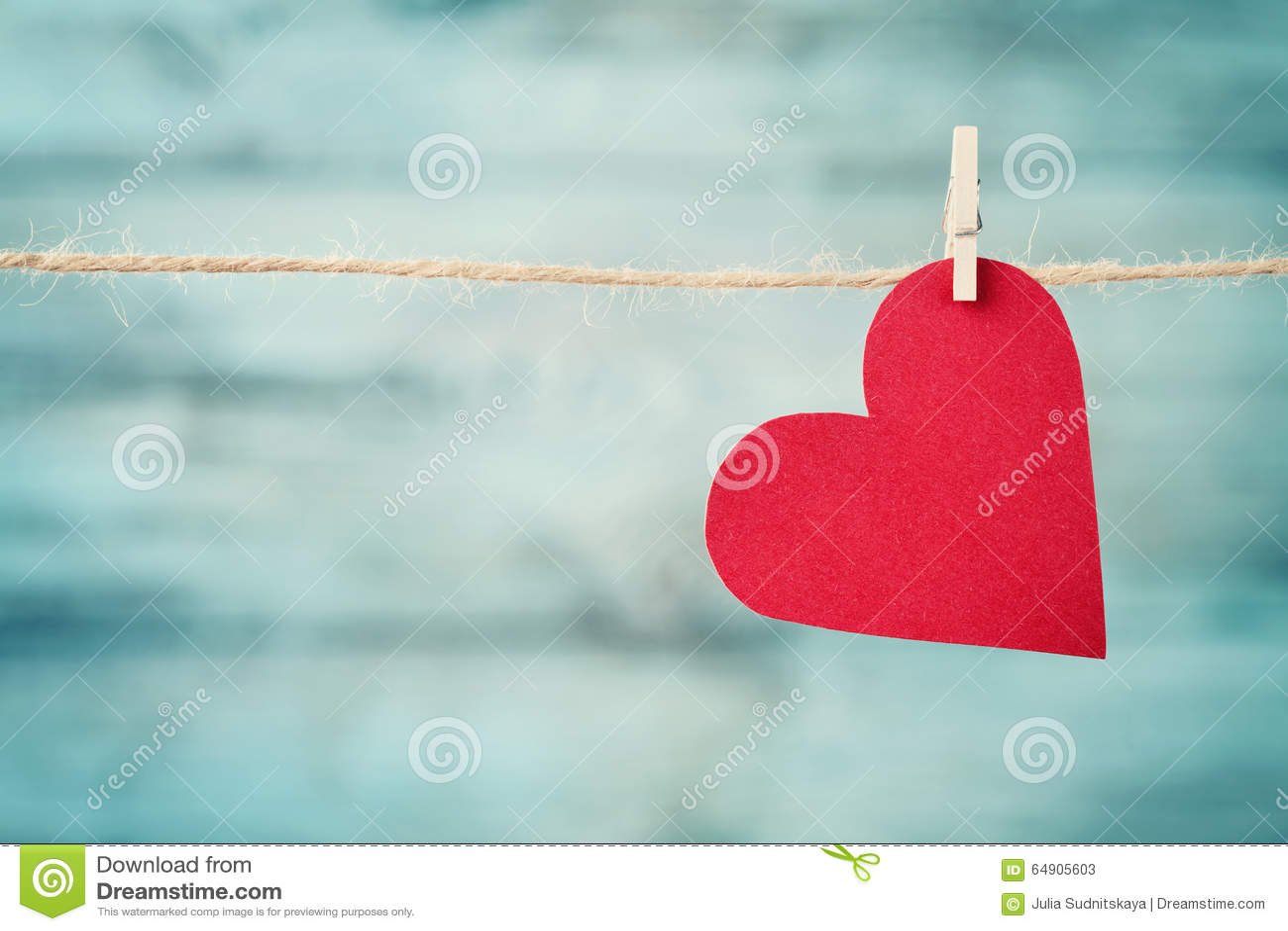 Coração de papel que pendura na corda contra o fundo de madeira de turquesa para o dia de Valentim
