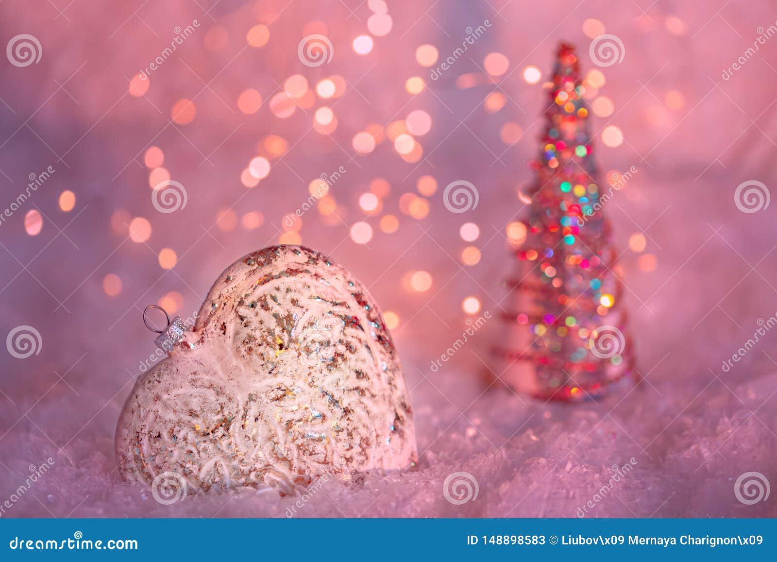 Coração de vidro em uma neve e fundo cor-de-rosa borrado tonificado do bokeh de brilho com luzes de incandescência Decora??o do N
