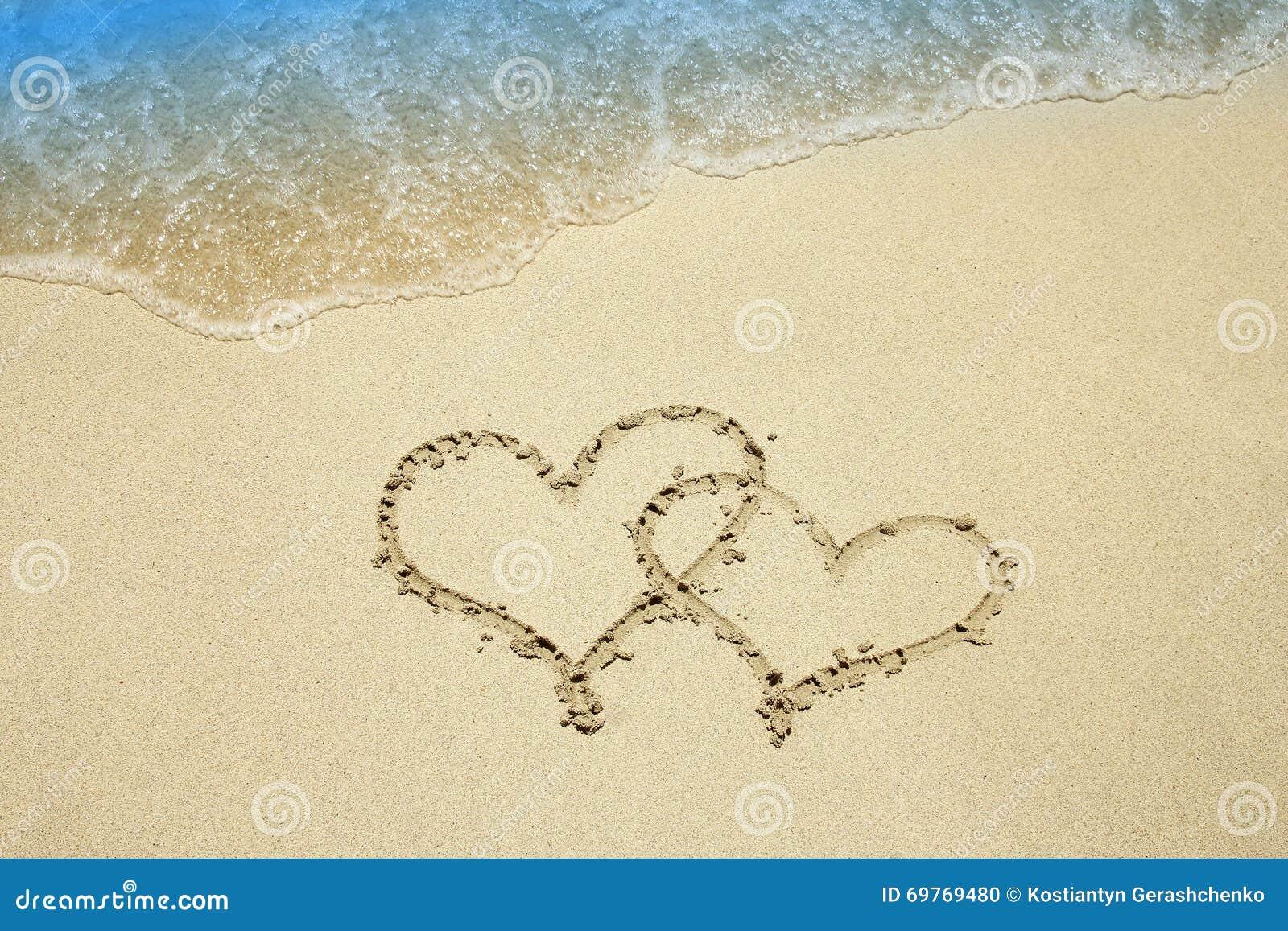 Coração na areia pelo mar
