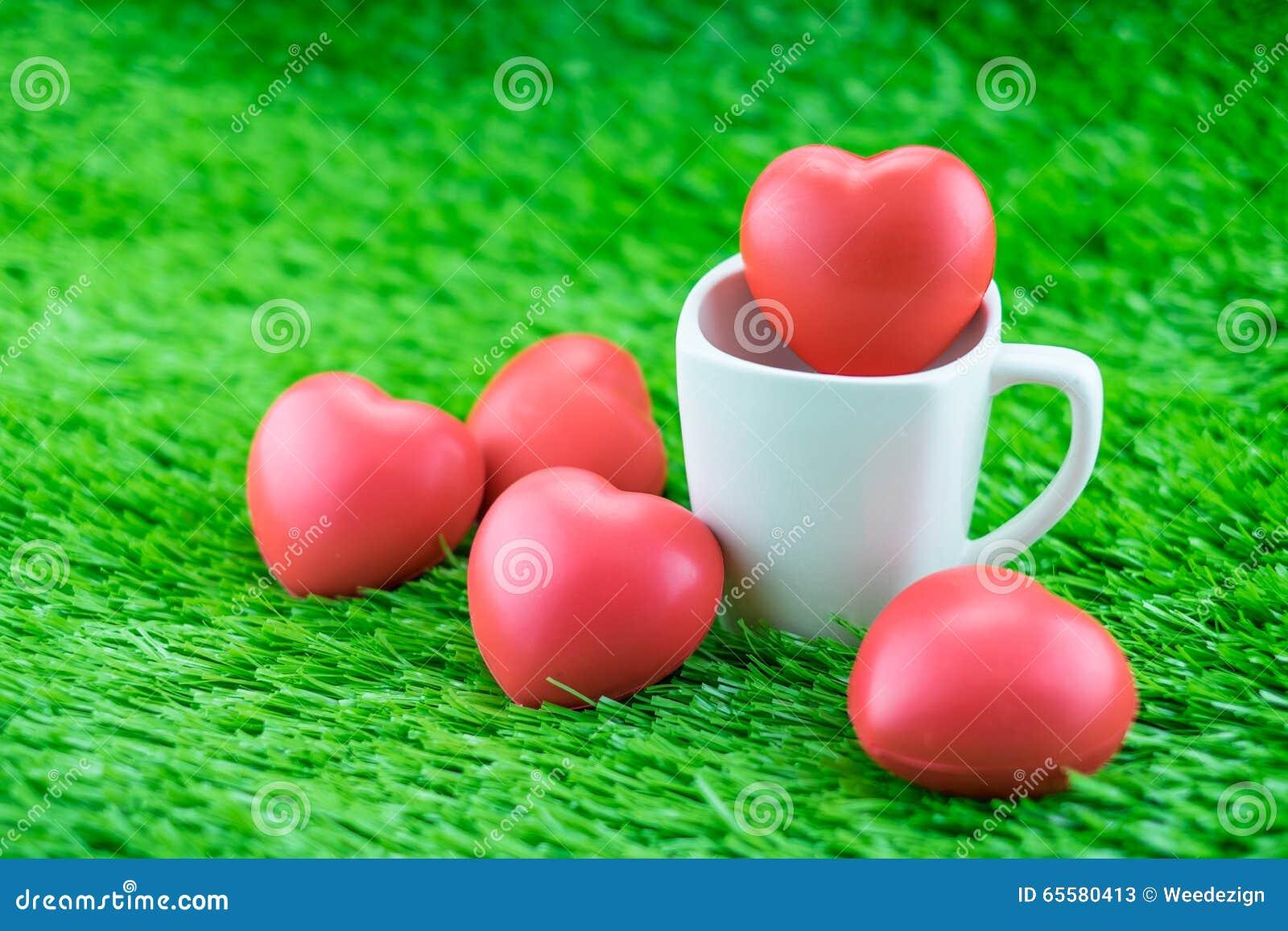 Coração vermelho no copo de café na grama, conceito do amor