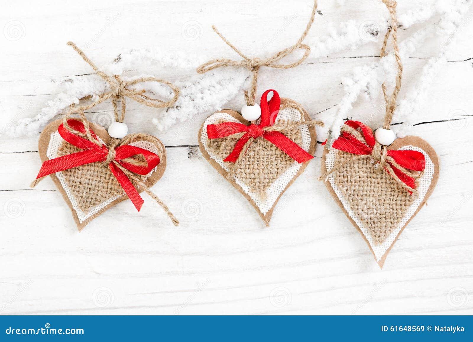 Corações decorativos no ramo coberto de neve no fundo de madeira