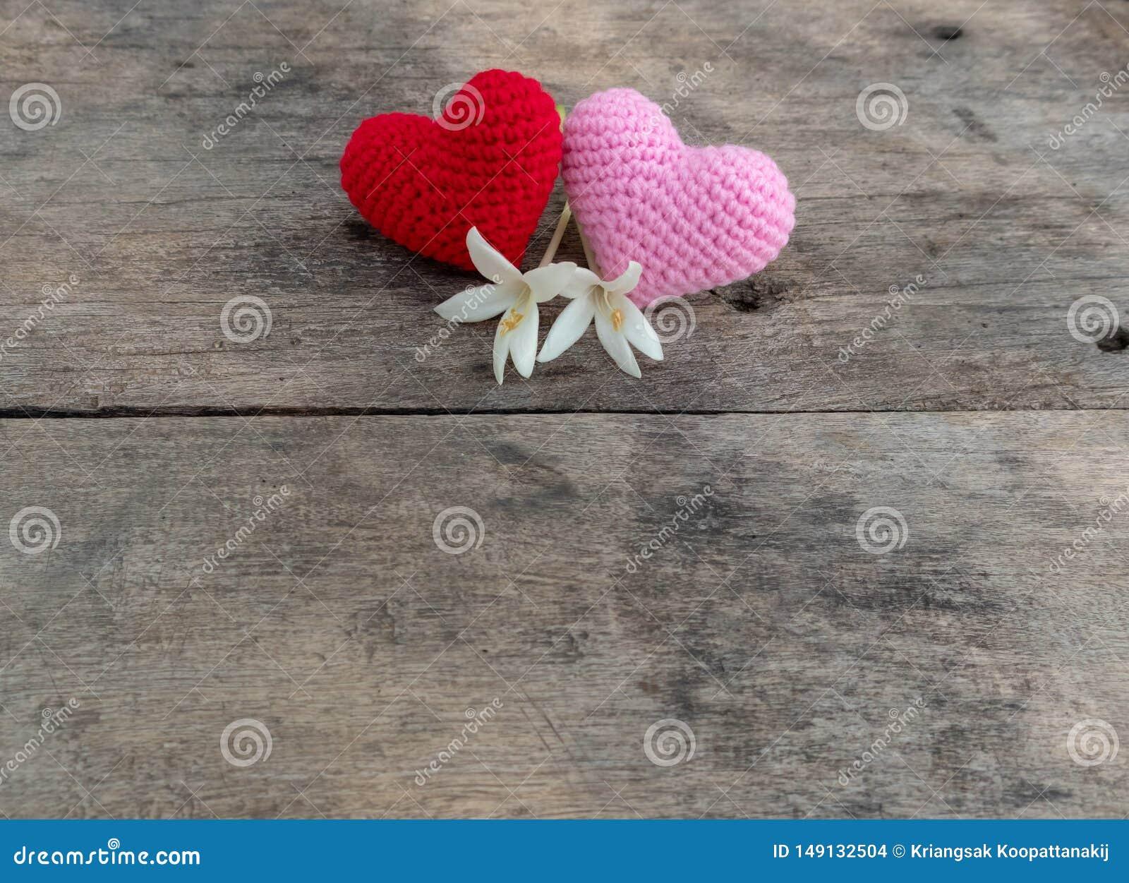 Cora??es nitting vermelhos e cor-de-rosa com as flores na tabela de madeira