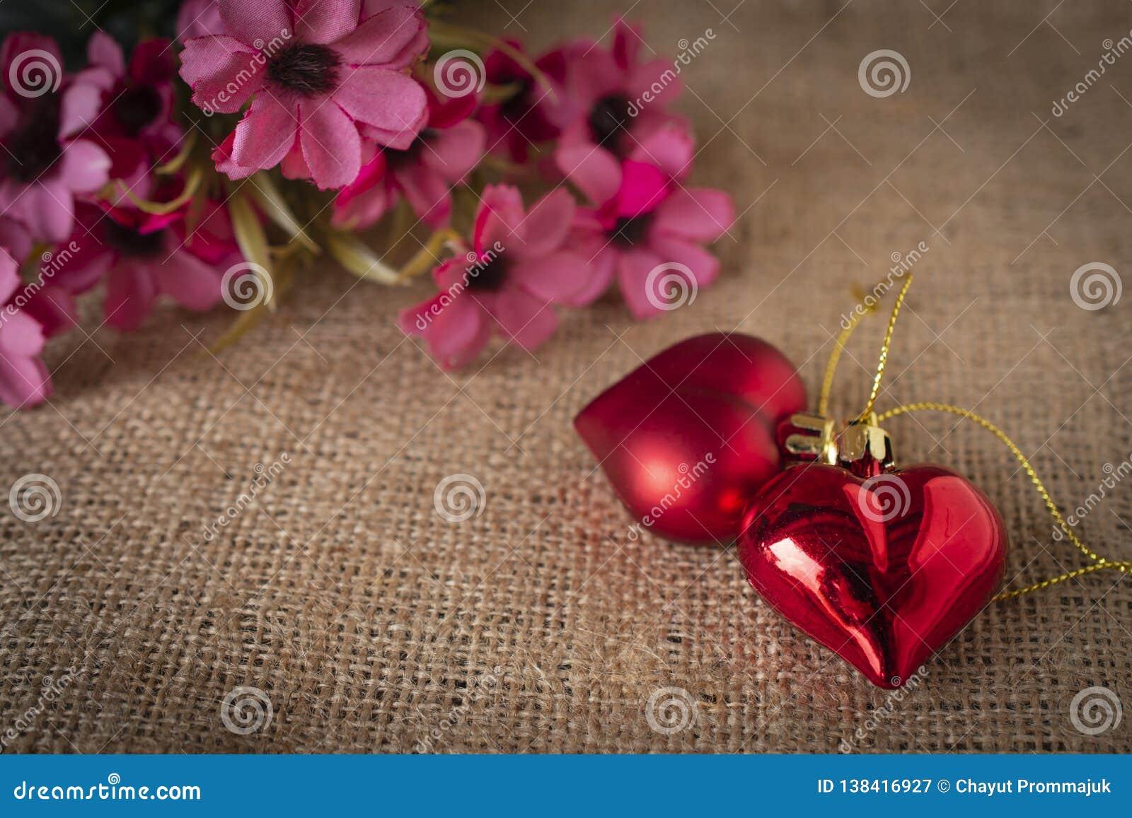 Corações plásticos vermelhos colocados no saco Há uma flor colocada na parte traseira esquerda