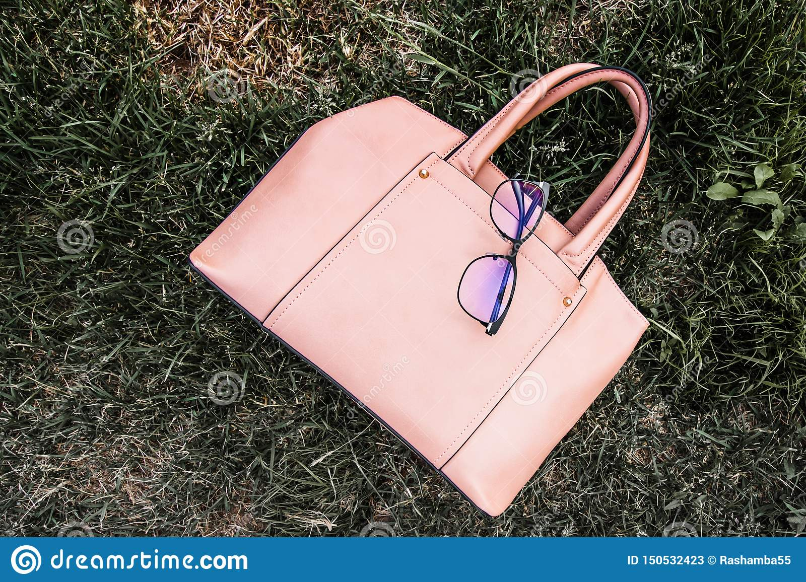 Coral leather female bag on the grass on the background of sky