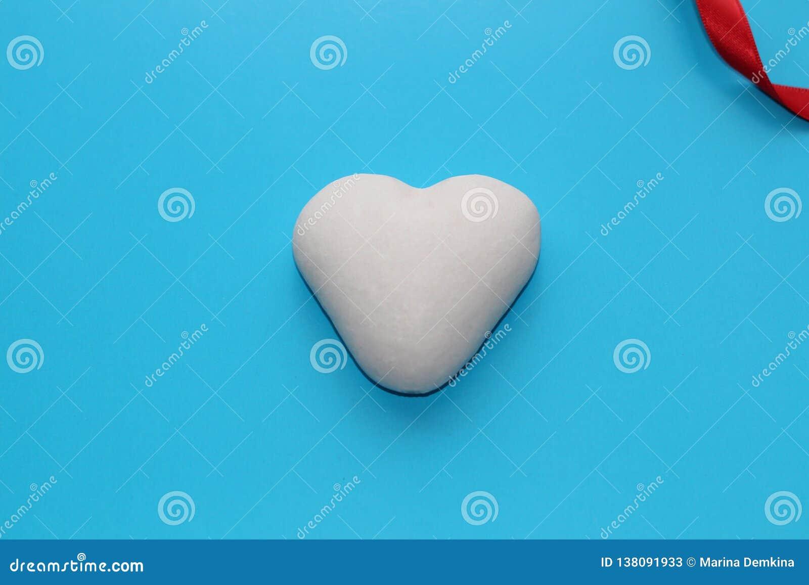 Corazón blanco en un fondo coloreado en honor del día de tarjeta del día de San Valentín