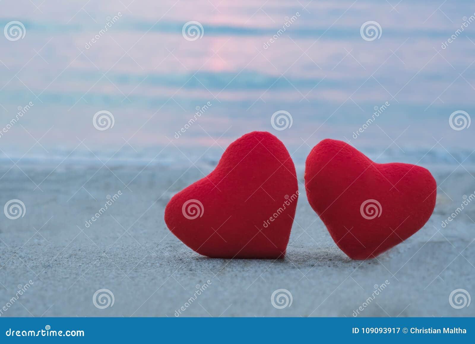 Corazón de dos rojos en la playa