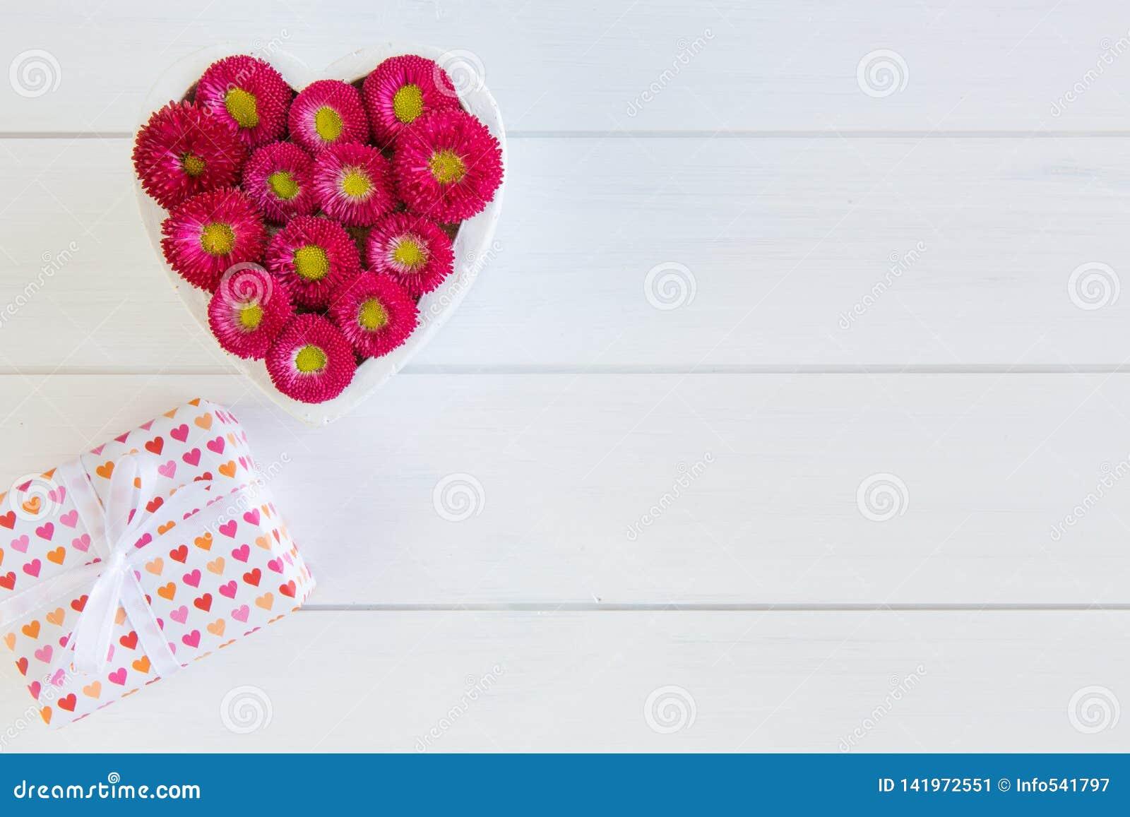 Corazón de la caja roja del Bellis y de regalo con el arco en fondo de madera en blanco