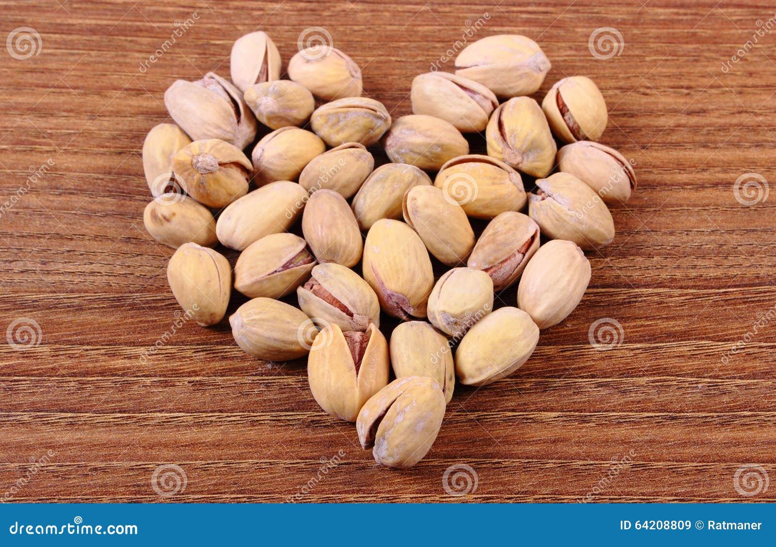 Corazón de las nueces de pistacho en la tabla de madera, consumición sana