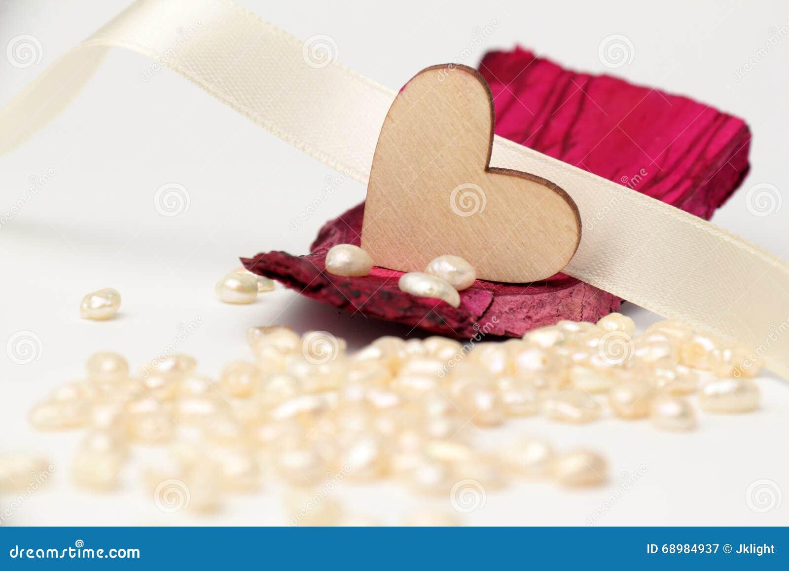 Corazón de madera en caoba de la madera de deriva con las perlas en el fondo