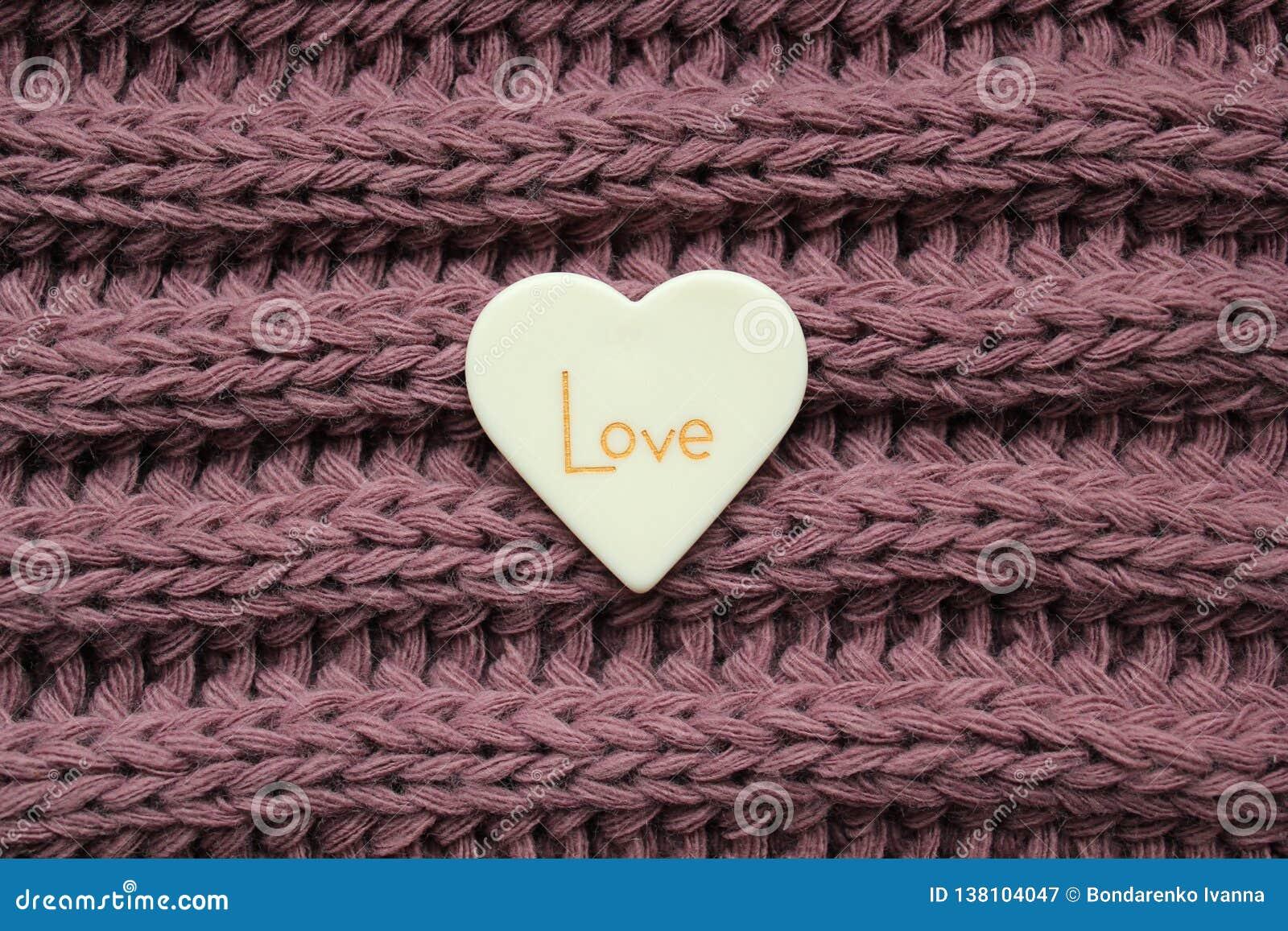 Corazón plástico blanco con palabra del amor en un fondo violeta hecho punto de la textura