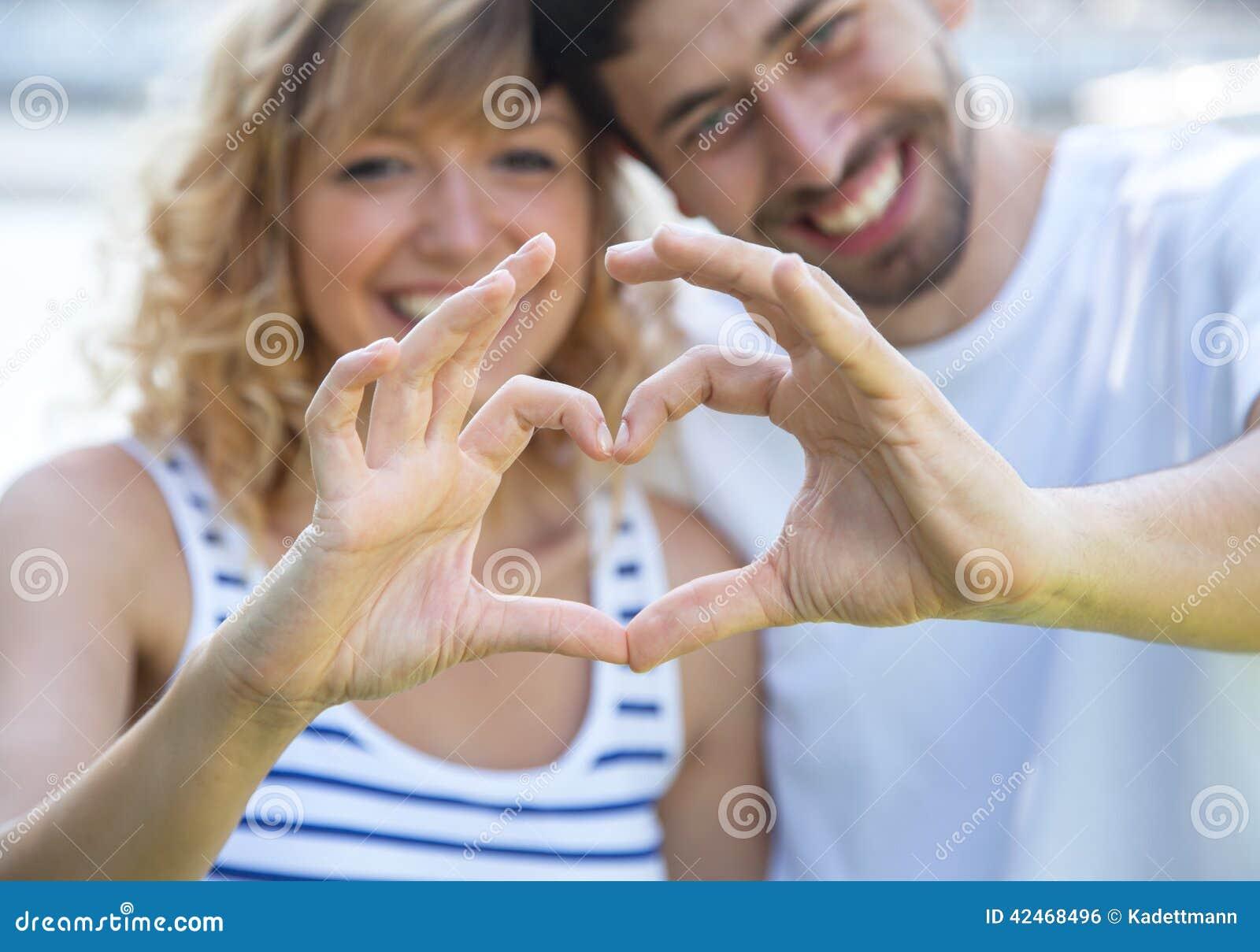 Corazón que muestra exterior de los pares felices del amor con los fingeres