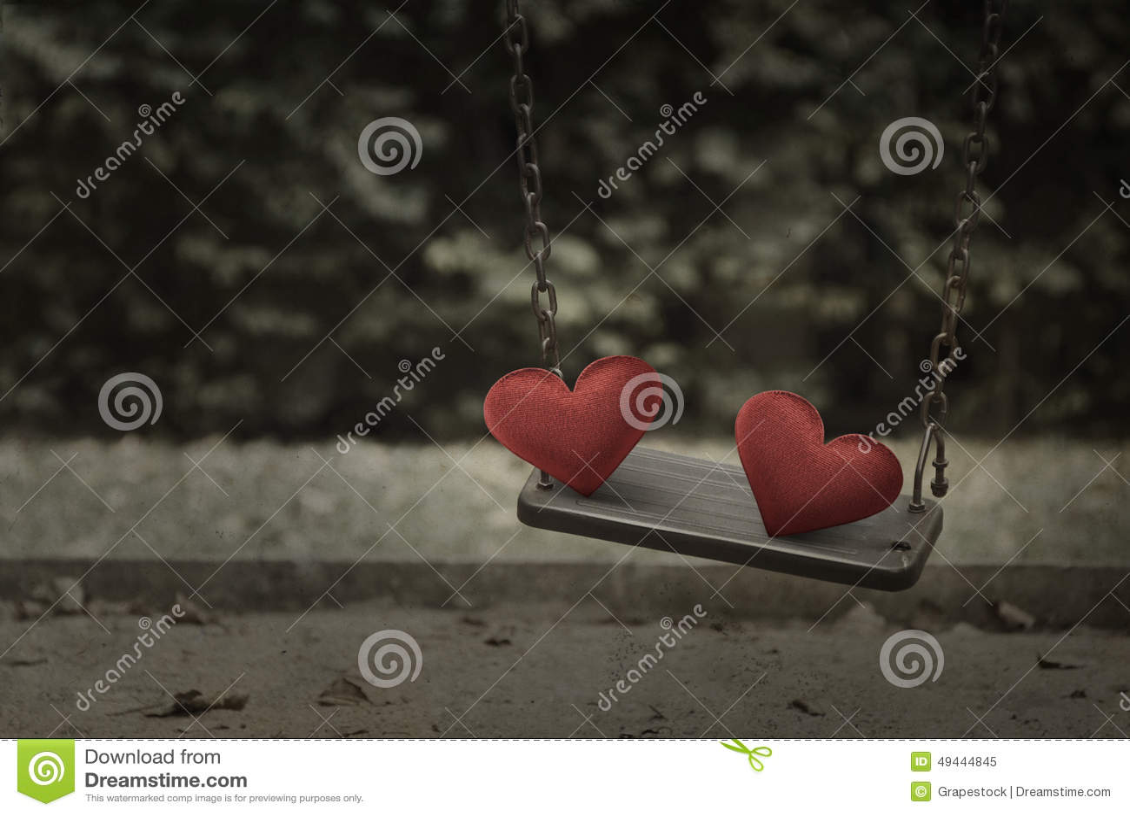 Corazón rojo de la tela en el oscilación del patio del metal del daño