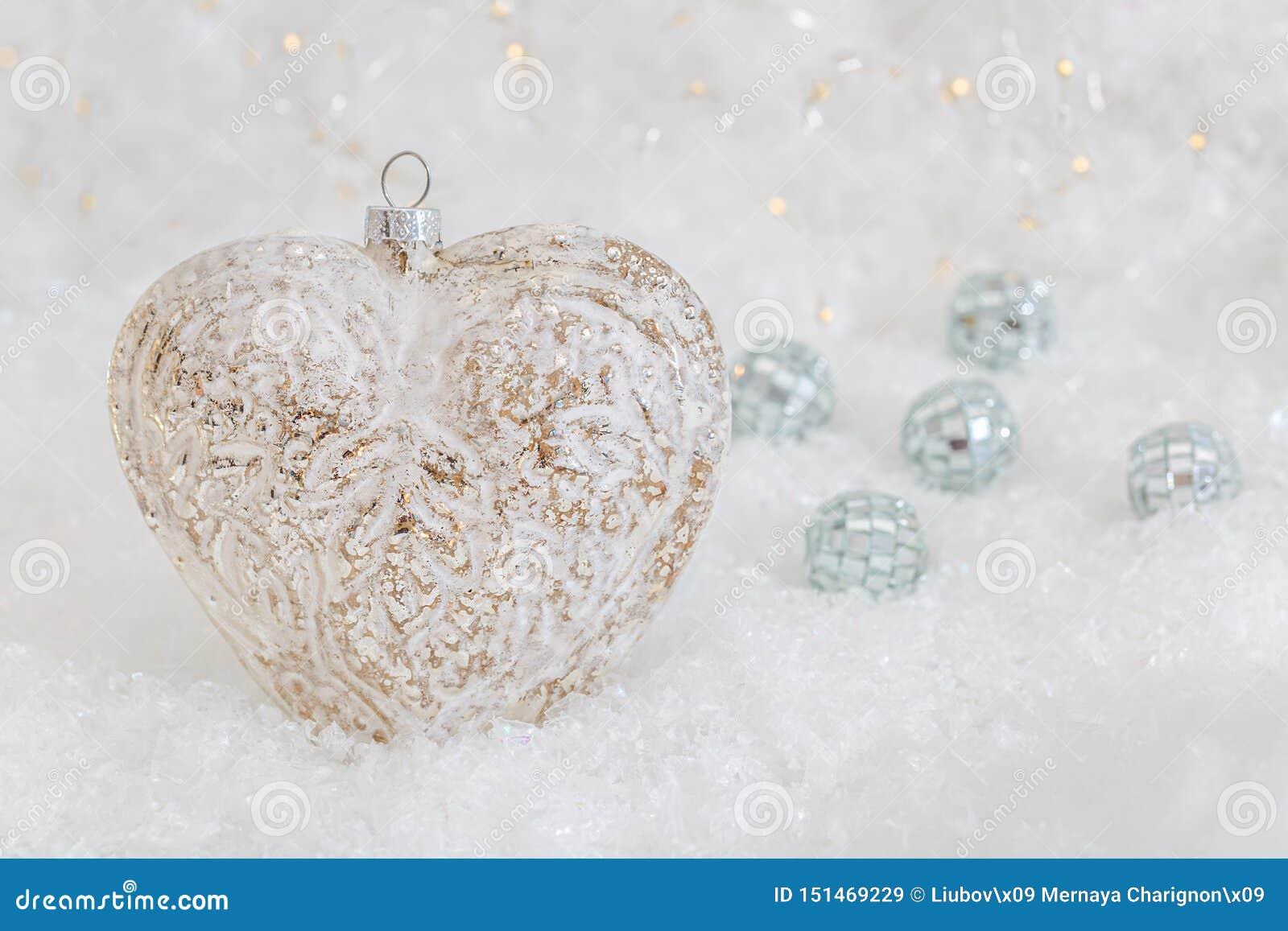Coraz?n de cristal en una nieve Fondo blanco borroso del bokeh que brilla con las luces que brillan intensamente Decoraci?n de la