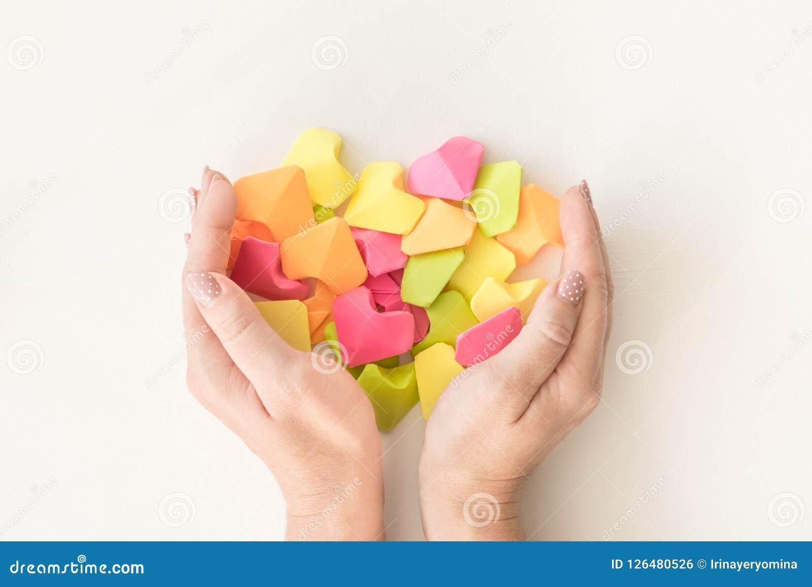 Corazones de papel de la papiroflexia multicolora en manos femeninas Manos de las mujeres llevando a cabo muchas el corazón brill