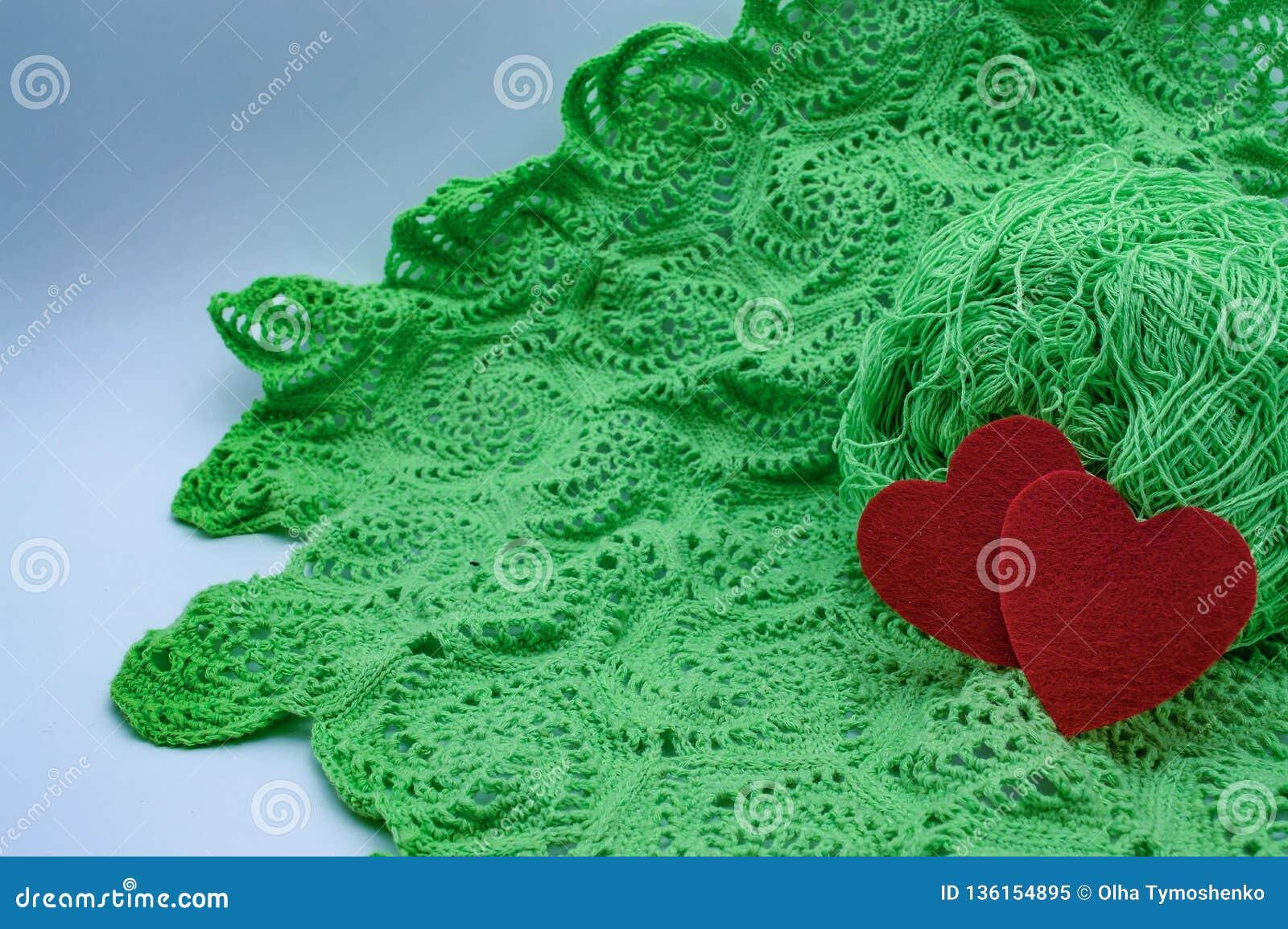 Corazones en el fondo de los hilos hechos punto de un verde del modelo hechos por las manos del amor