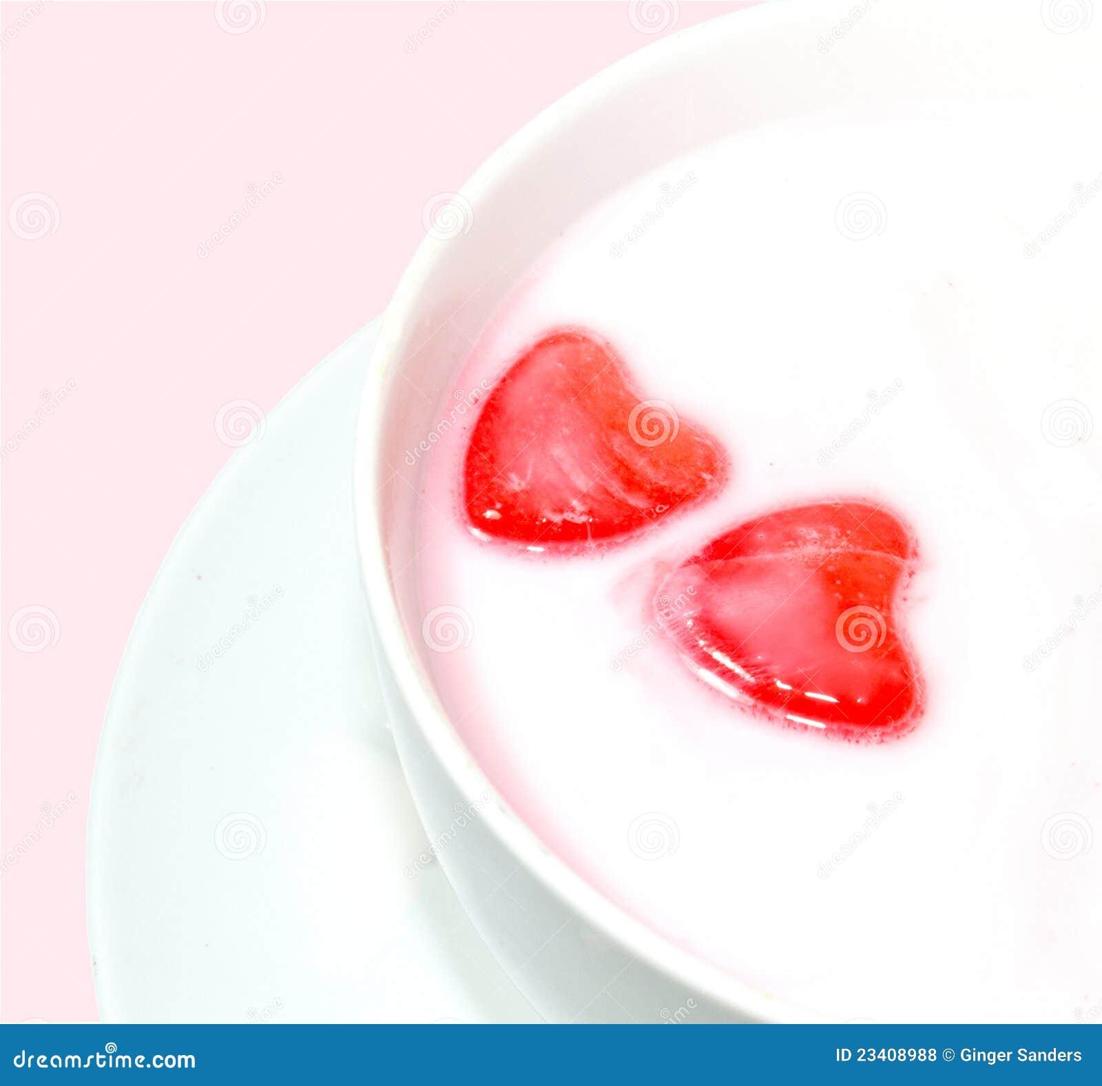 Corazones rojos del amor en leche
