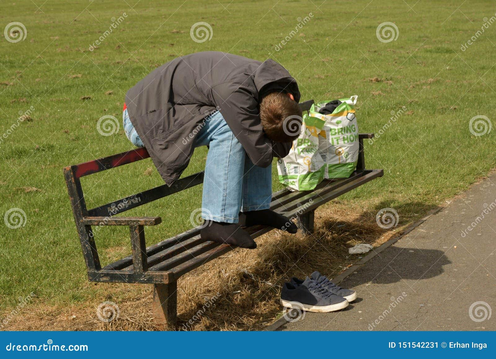 Corby, U ? , Στις 20 Ιουνίου 2019 - άστεγος ύπνος ατόμων σε έναν πάγκο έξω