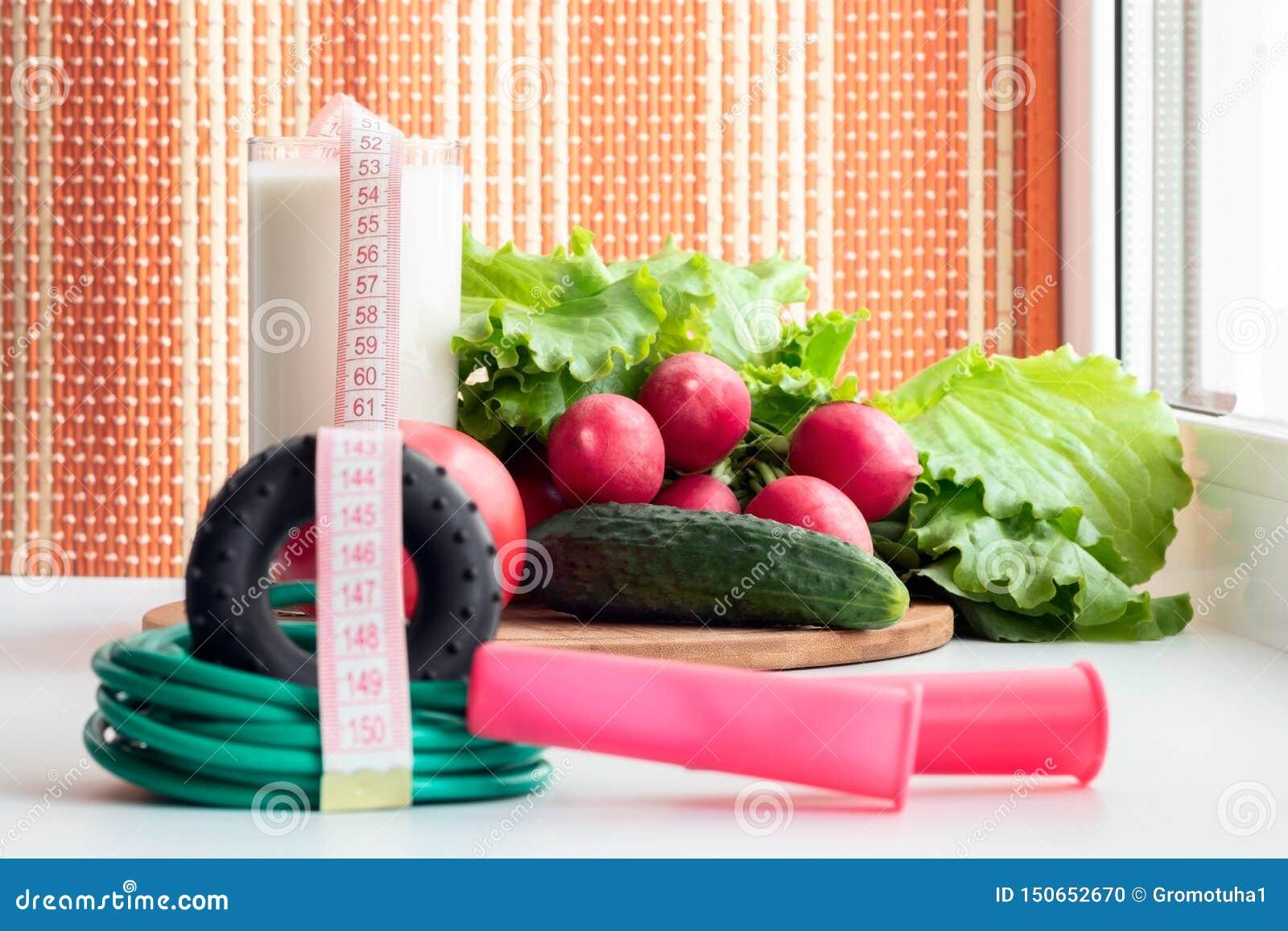 Corda e vegetais ginásticos de salto para uma dieta saudável - o tomate, o pepino, o rabanete e a alface estão na tabela perto da