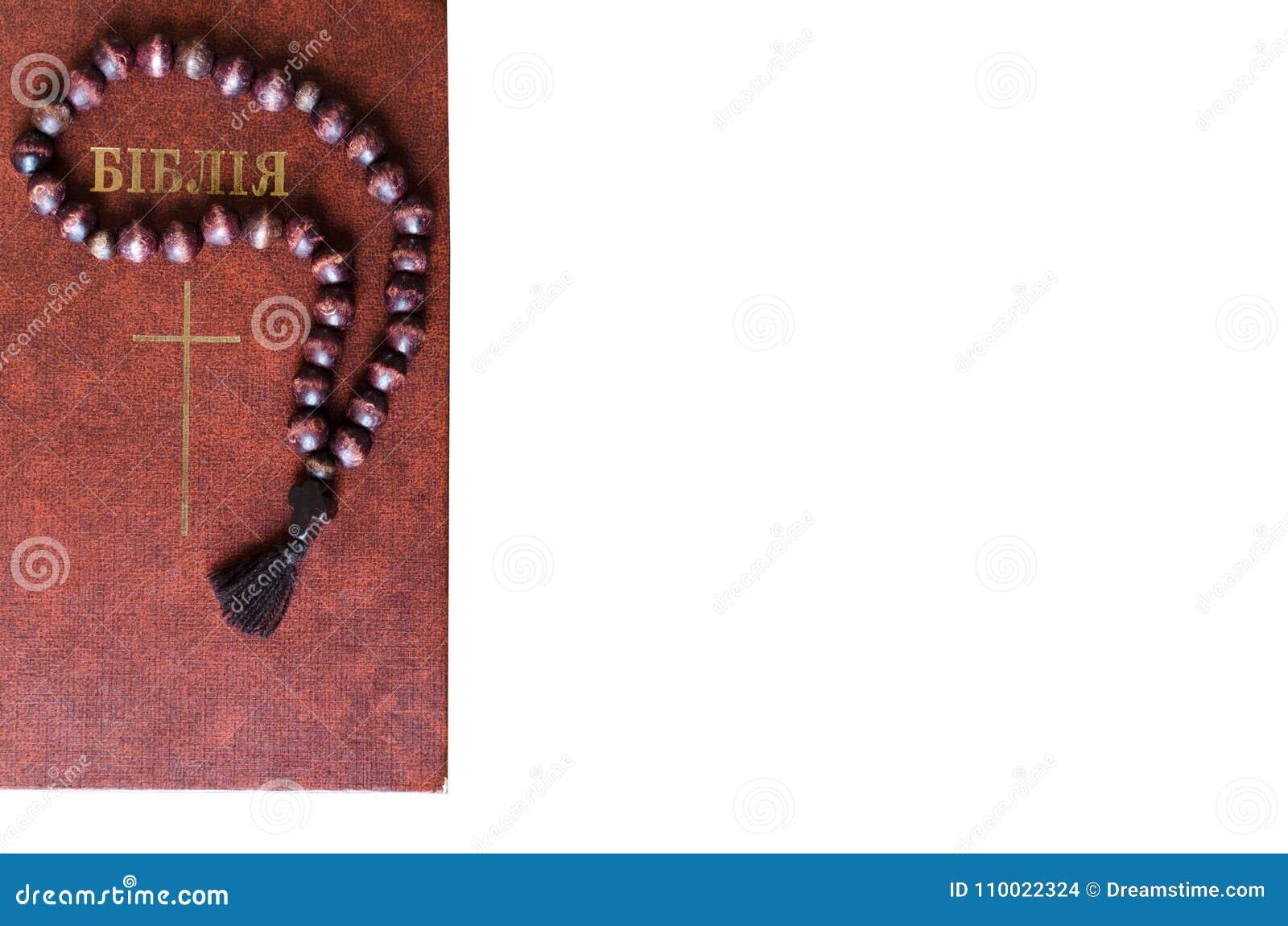 Corda isolata di preghiera Corda di legno di preghiera con la bibbia isolata su fondo bianco