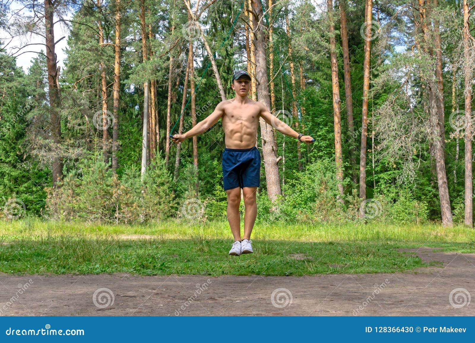 Corde à sauter de jeune homme dans une forêt de pin