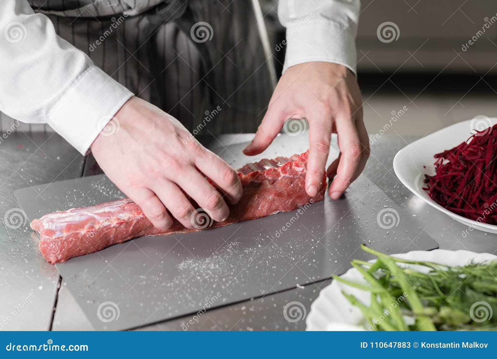 Corderos raros listos para el adobo con romero El cocinar con el fuego en sartén Cocinero profesional en una cocina de