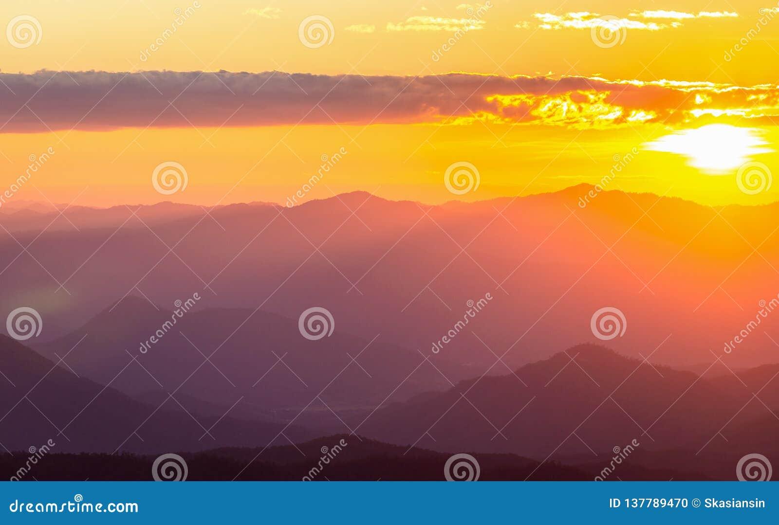 Cordillera nebulosa con el cielo dramático de la puesta del sol