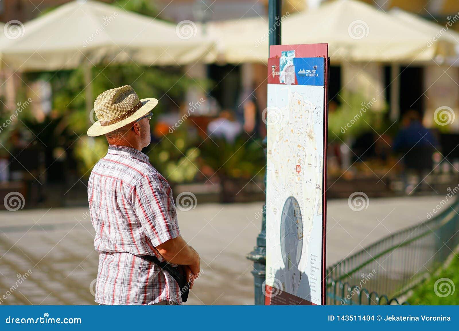 CORFOU, GRÈCE, LE 18 OCTOBRE 2018, un touriste regarde avec l intérêt une carte de touristes dans la place de Dimarcheio