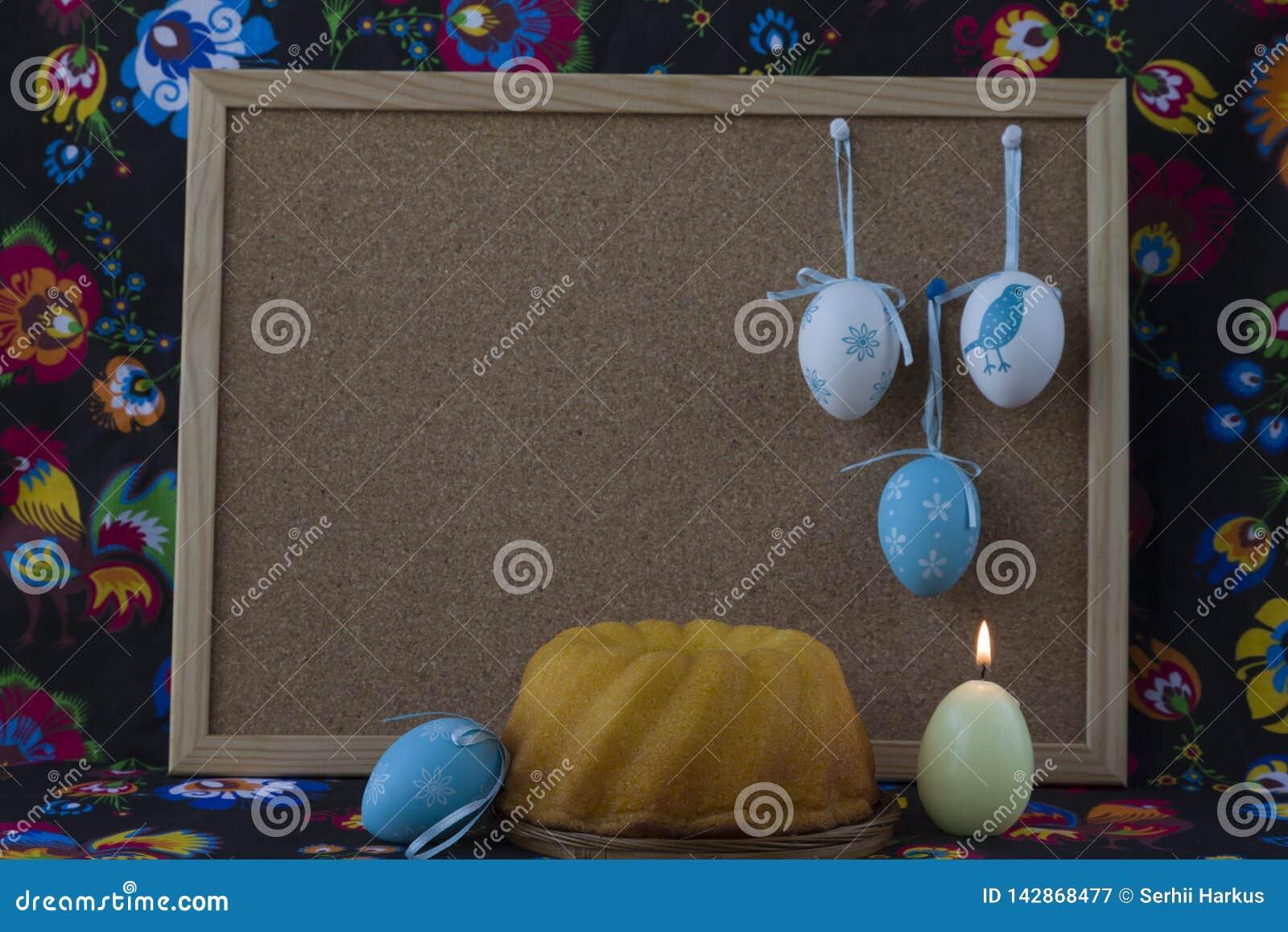 Διακόσμηση Πάσχας με τα άσπρα και μπλε αυγά στο χρωματισμένο υφαντικό υπόβαθρο με το corkboard